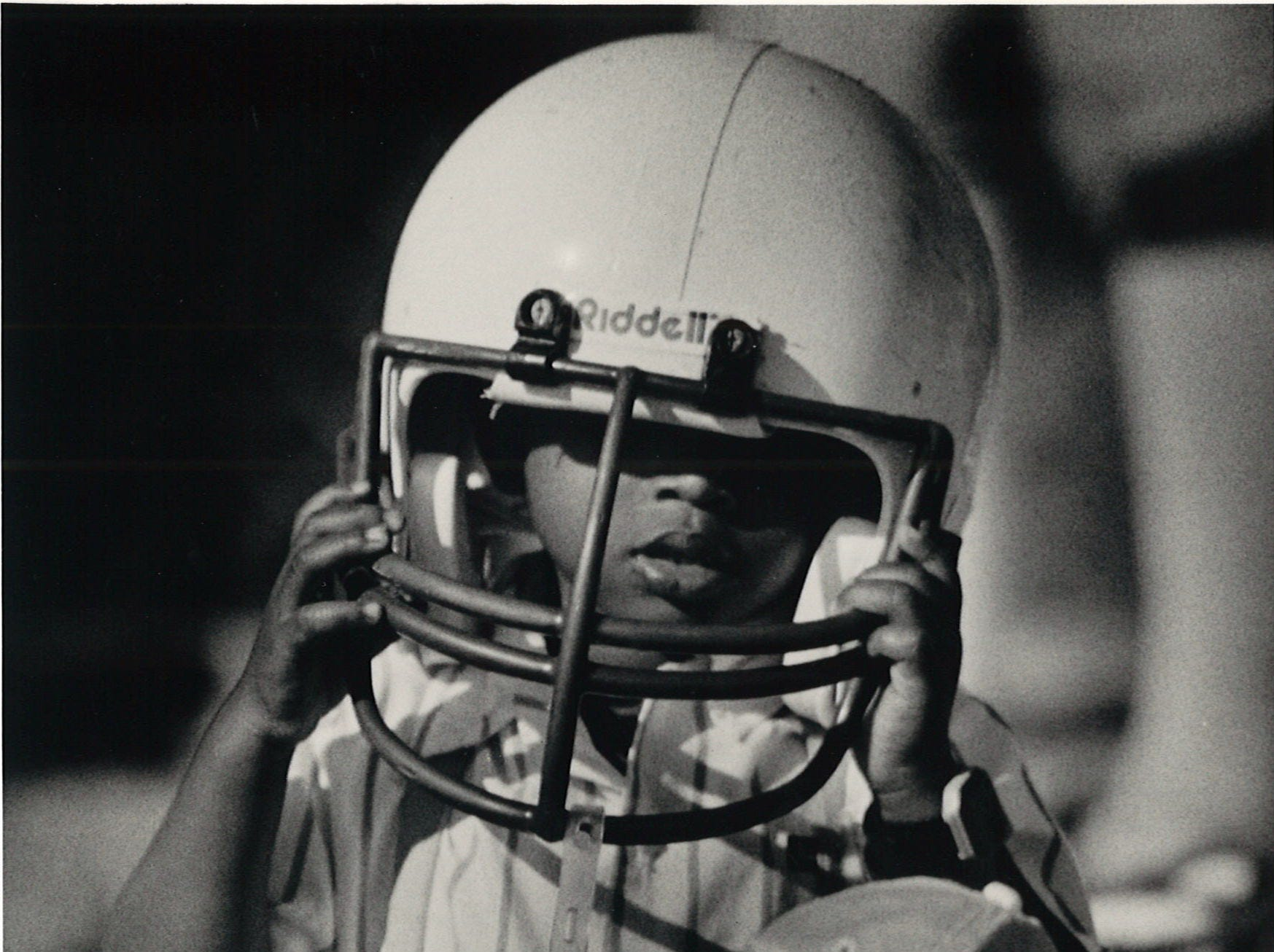 Finding that three years is not enough to fill dad's shoes, JOhnathan Denmon, 3, also finds that a helmet is just as hard to fill. His father, Ernest Denmon, was playing for the LULAC Broncos at the annual Menudo Bowl on Jan. 30, 1988.