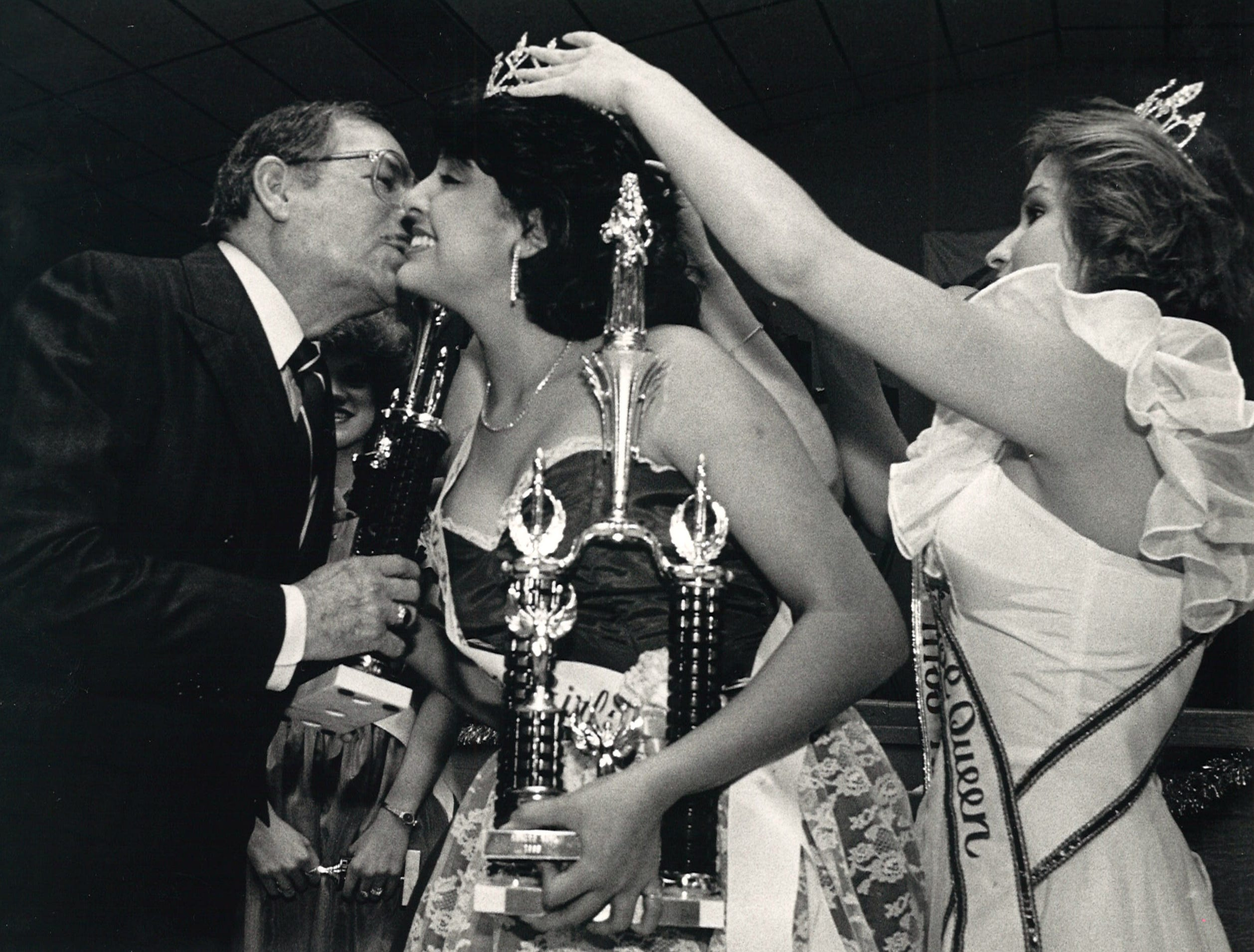Ray High School student, Merida May Mendoza, was crowned Menudo Bowl Queen at the Stardust Ballroom on Jan. 25, 1985. She received a trophy and a kiss from presenter Art Garcia as the 1984 queen Evelyn Farias assisted with her crown.
