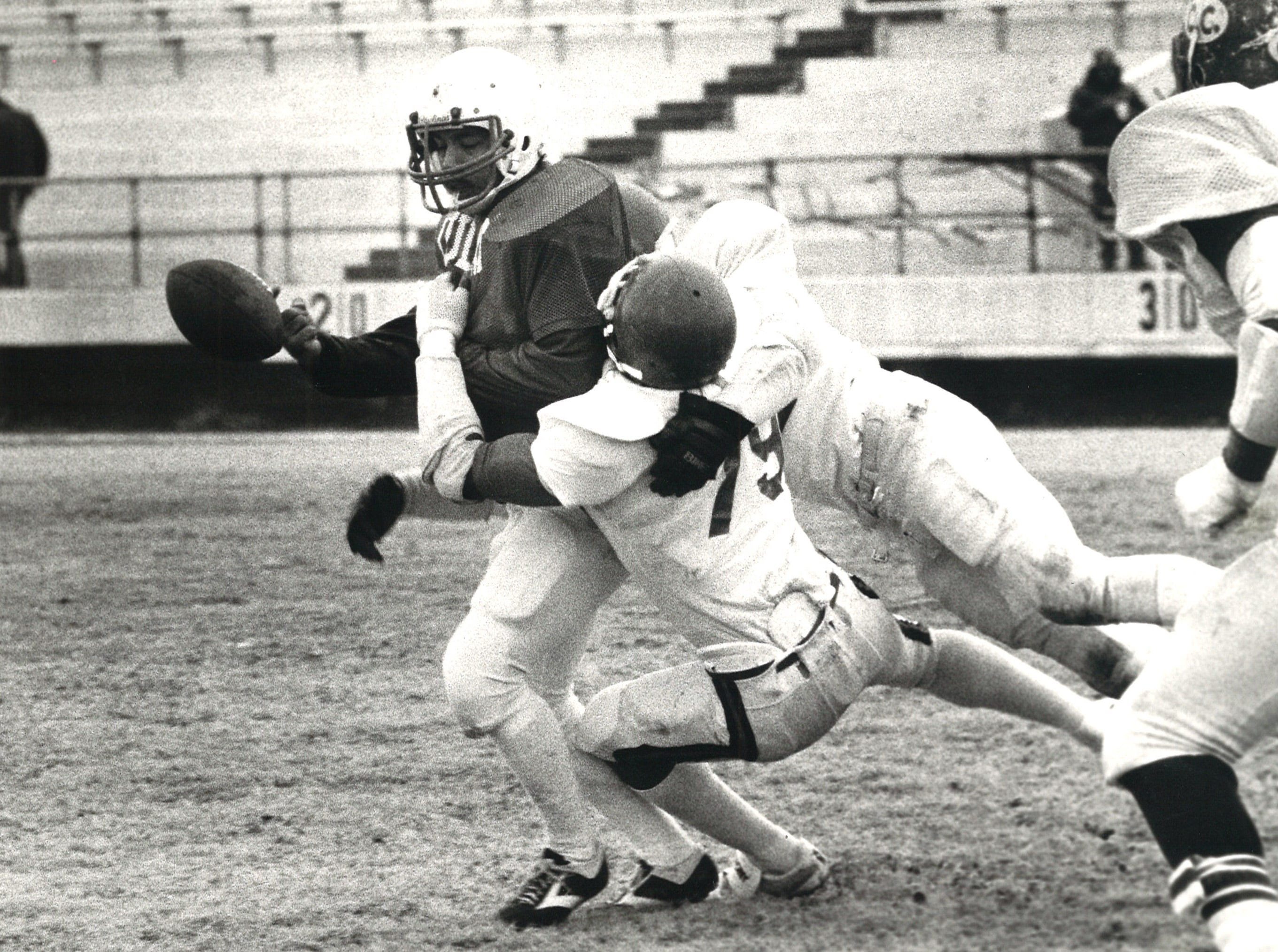 No. 11 Lupe Gutierrez, quarterback for the LULAC Broncos, fumbles the ball during the first quarter of the annual Menudo Bowl at Buc Stadium on Jan. 14, 1984. Causing the fumble is No. 79, Herrow Collins  and No. 32 Dan Garcia of the Corpus Christi Army Depot Cobras.
