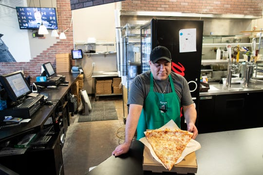 Manager Isidro Navarro holds one of the Brooklyn Pie Co.'s giant pizza slices at its North Padre Island location. The Brooklyn Pie Co. is opening a new location in the Southside at 6181 Saratoga Blvd., near Walmart.