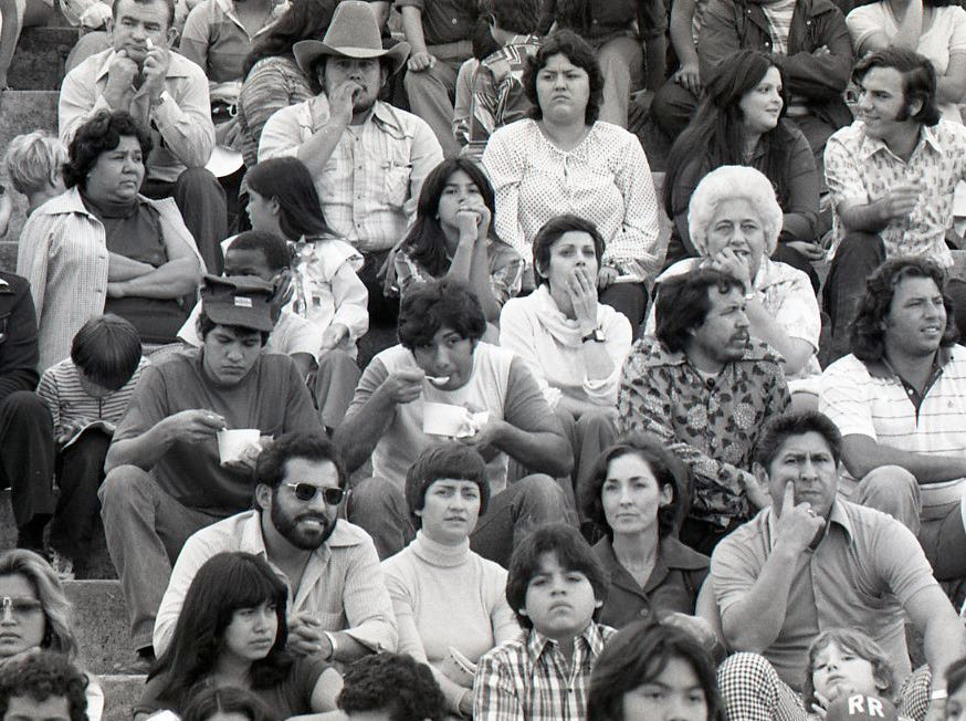Two fans divide their attention between their bowls of menudo and the Menudo Bowl football action on Jan. 7, 1978.