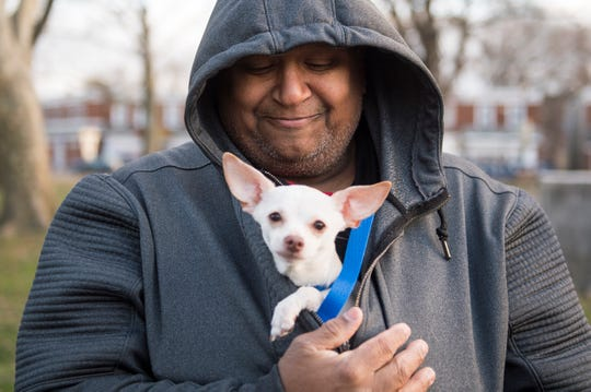 Harold Santiago waits in line with his chihuahua Rico as the Animal Welfare Association offers free pet care Wednesday, Nov. 28, 2018 at Yorkship Square in Camden, N.J.