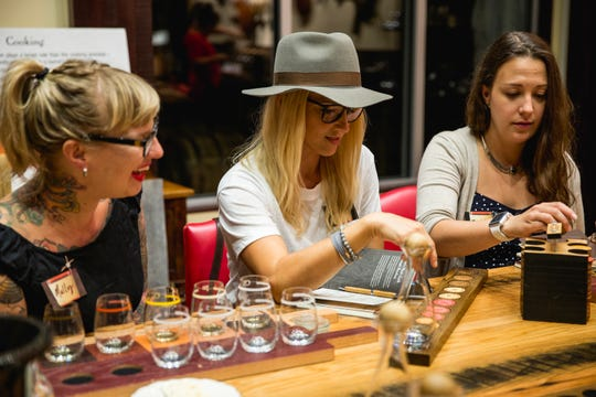 Left to right, Bar owner and Mixologist Molly Wellmann, Britney Ruby, President of Jeff Ruby Culinary Entertainment, and  Mariel Wood, executive assistant, taste and select different varieties of Maker's Mark to blend into a private label bourbon.