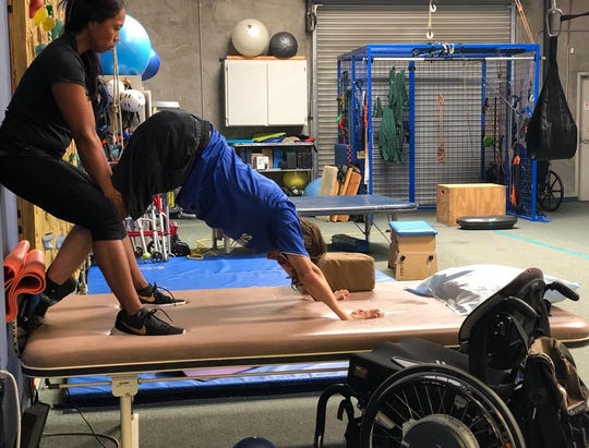 Elliot works on stretching during a physical therapy session.