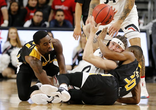 Cincinnati Bearcats guard Logan Johnson (0) gets the ball away from a pileup in the first half of the NCAA basketball game between the Cincinnati Bearcats and the Arkansas-Pine Bluff Golden Lions at Fifth Third Arena in Cincinnati on Tuesday, Nov. 27, 2018.