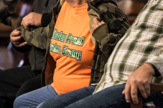 """Judy Manley removes her coat to reveal a """"Rhoden Proud, Rhoden Strong"""" t-shirt at the Pike County Courthouse for George's arraignment on Wednesday, November 28, 2018 in Waverly, Ohio."""
