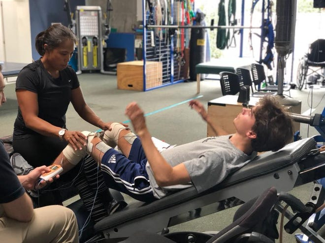 A physical therapist works with Elliot Feltner at a physical therapy center in California.