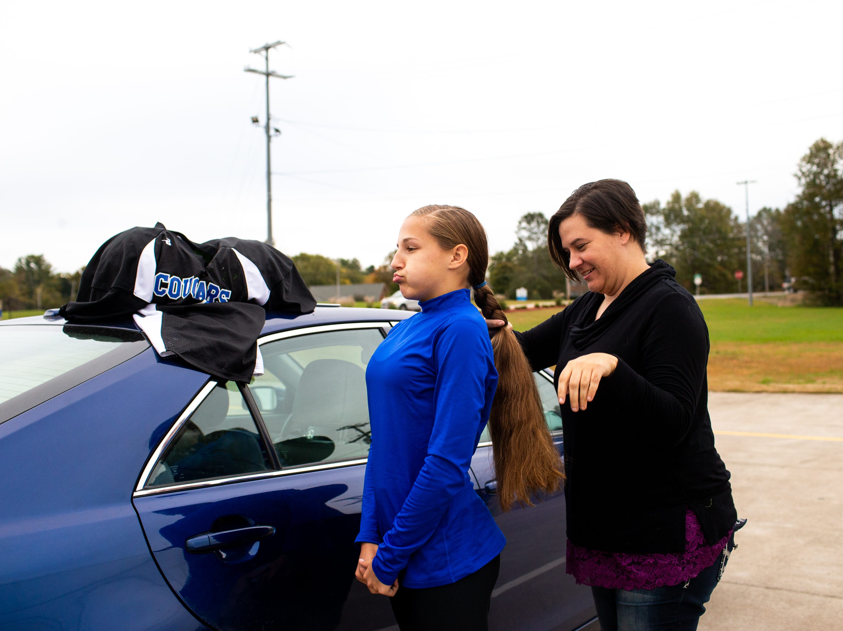 Deidre Freeman braids her daughter, Elizabeth Cundiff's, hair in the parking lot before the game at the Clarksville Academy Sports Complex Thursday, Oct. 25, 2018, in Clarksville, Tenn. During a game, Elizabeth's ponytail is tucked into her jersey so other players won't pull it.