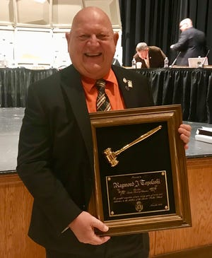 Linden Board of Education President Raymond J. Topoleski holding a plaque he was given at the board's Nov. 20 meeting in honor of more than 18 years of service.
