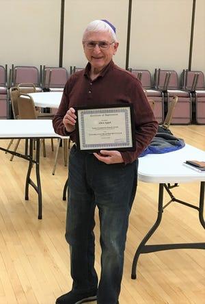 Allen Appel holding the certificate evidencing the Mensch Award.