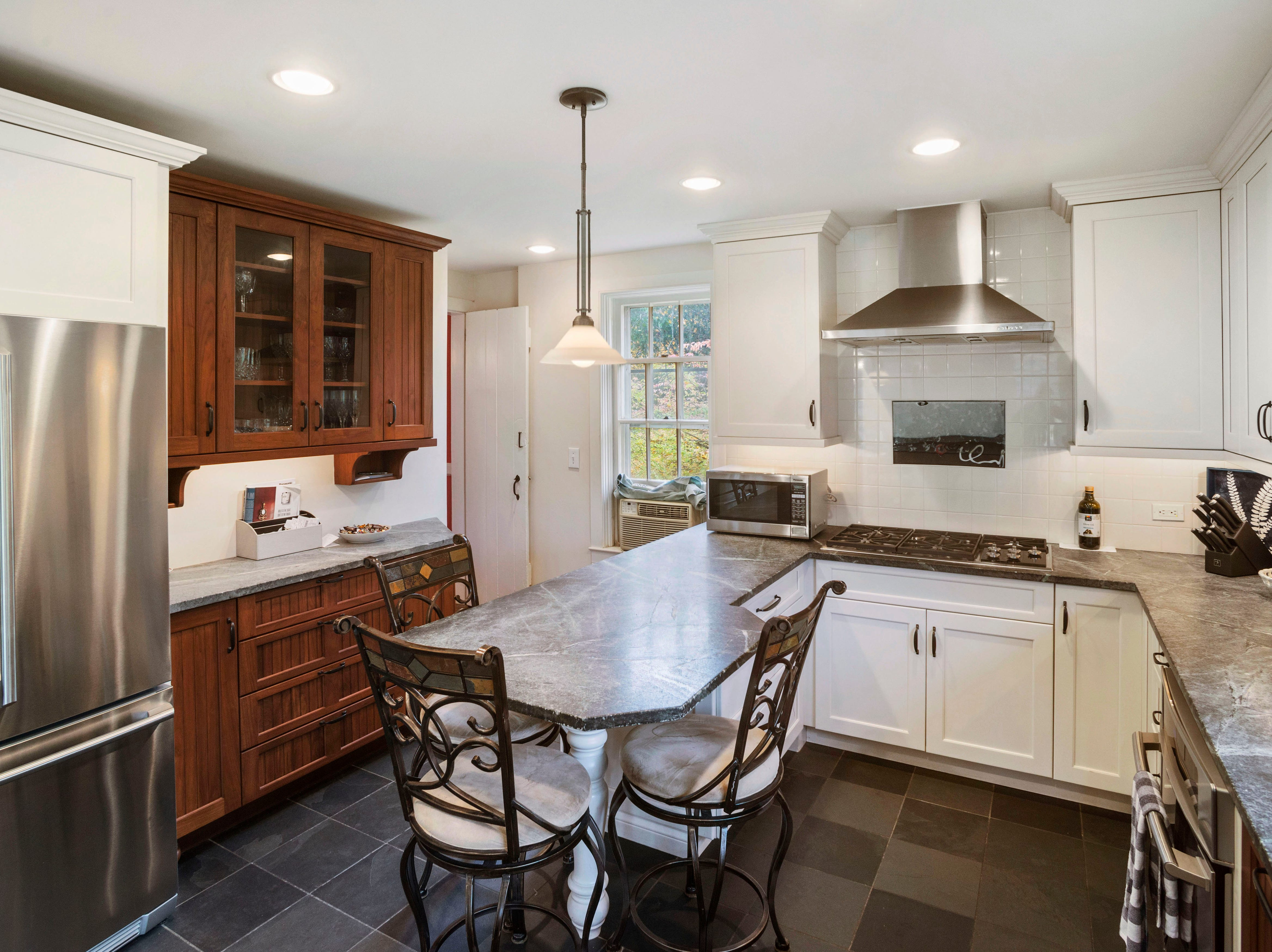 The kitchen in the Murphy-Voorhees home has been updated to 21st-century standards with a side-by-side refrigerator with a bottom freezer, modern cabinets, a slate floor, recessed and pendant lights and a modern cooktop with an equally modern hood.