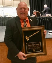 Linden Board of Education President Raymond J. Topoleski holding a plaque he was given at the board's Tuesday, Nov. 20, meeting in honor of more than 18 years of service.