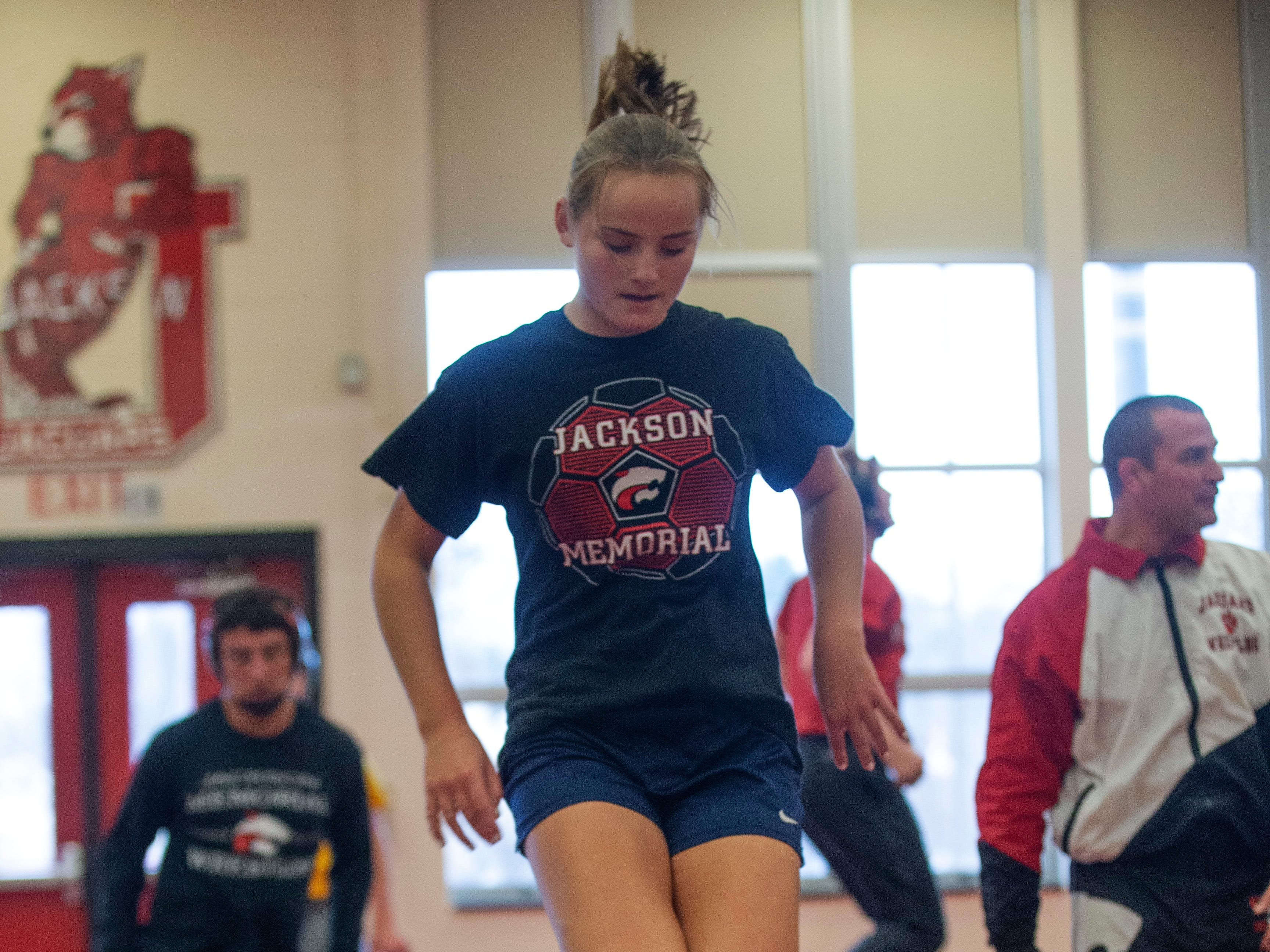 Hannah Reese jumps over Avery Meyers during warm up exercises. NJSIAA is offering wrestling for girls this year and they will participate in an all girls tournament at the end of the season. Jackson Memorial Wrestling is fielding a full girls team this year. Boy and girls practice together although mostly match up with partners of their own sex for most drills.