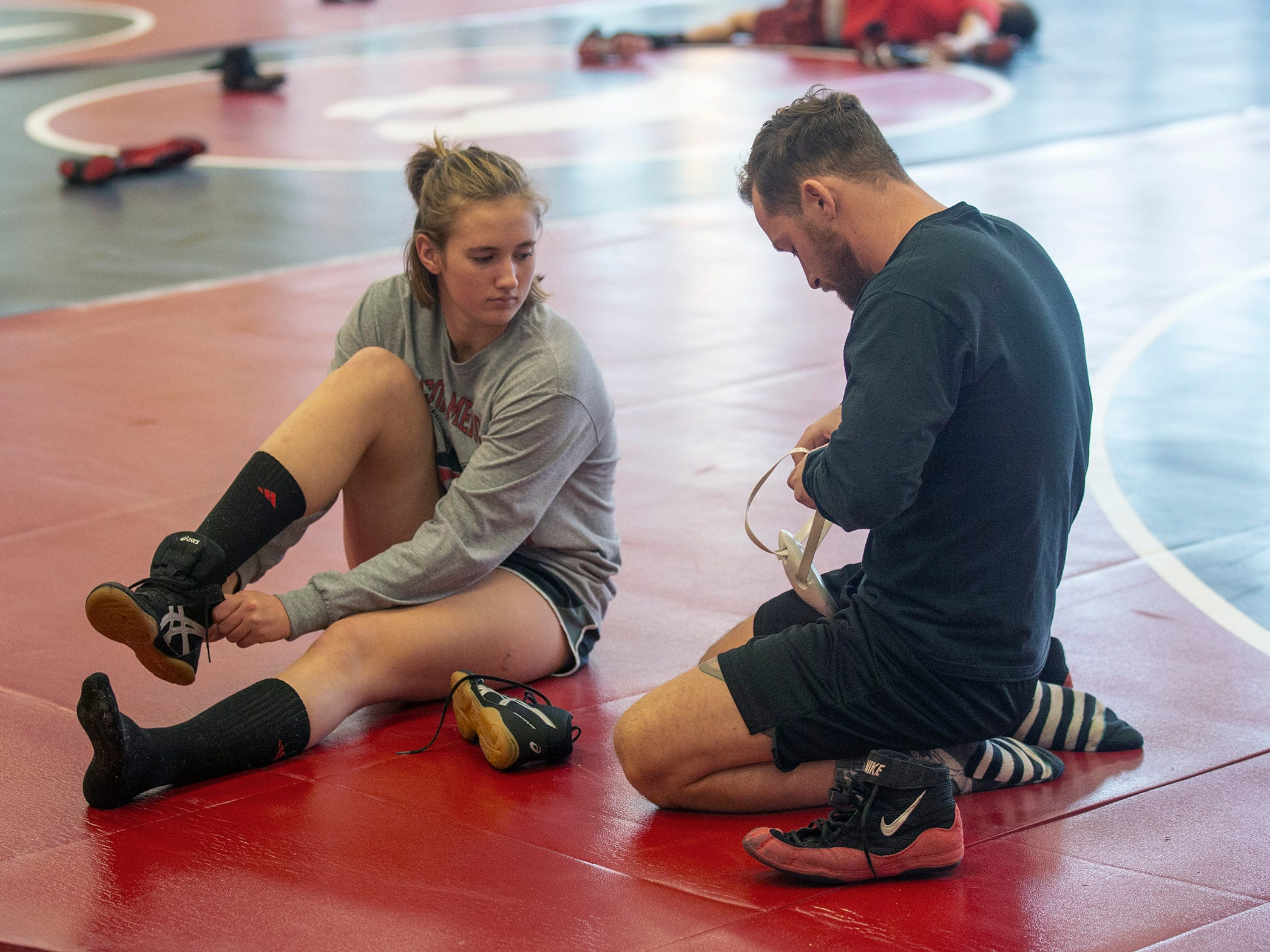 Abby Stanberry gets help with her headgear at the start of practice. NJSIAA is offering wrestling for girls this year and they will participate in an all girls tournament at the end of the season. Jackson Memorial Wrestling is fielding a full girls team this year. Boy and girls practice together although mostly match up with partners of their own sex for most drills.