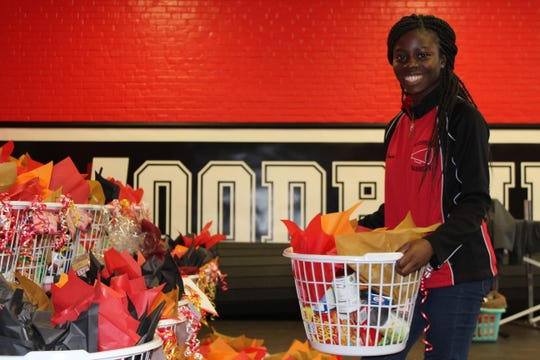 Woodbridge senior Comfort Akuamoah-Boateng helps move Thanksgiving baskets for distribution to families in need on Tuesday, Nov.21. Woodbridge High School's Interact Club prepared 66 baskets for donation through the We Feed Woodbridge organization.