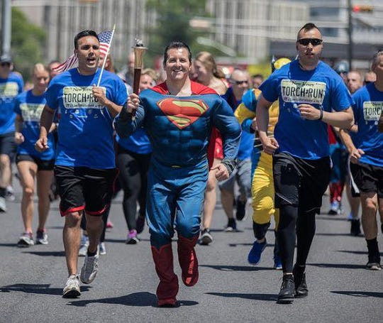 Superman from Heroes 4 Heroes running the torch for the Special Olympics.