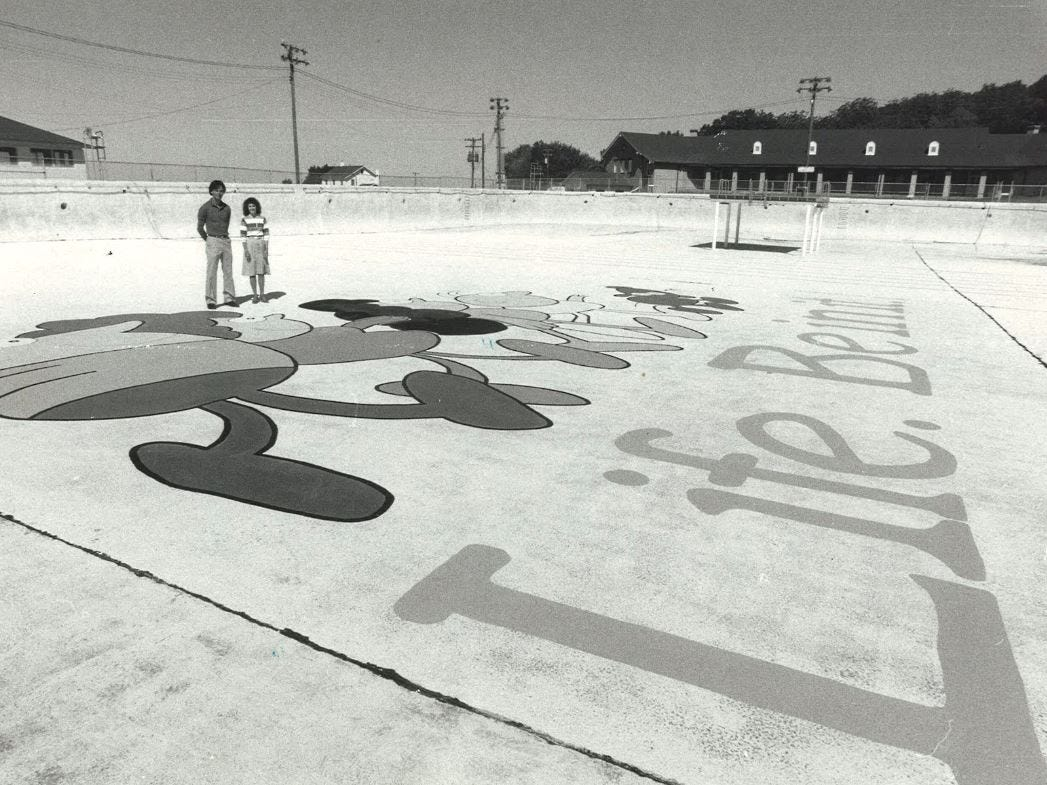 """From 1985: Ed Wallace and Christine Larson of the Des Moines Playground and Recreation Association, have had a mural saying """"Life. Be in it."""" painted on the bottom of the Camp Dodge pool."""