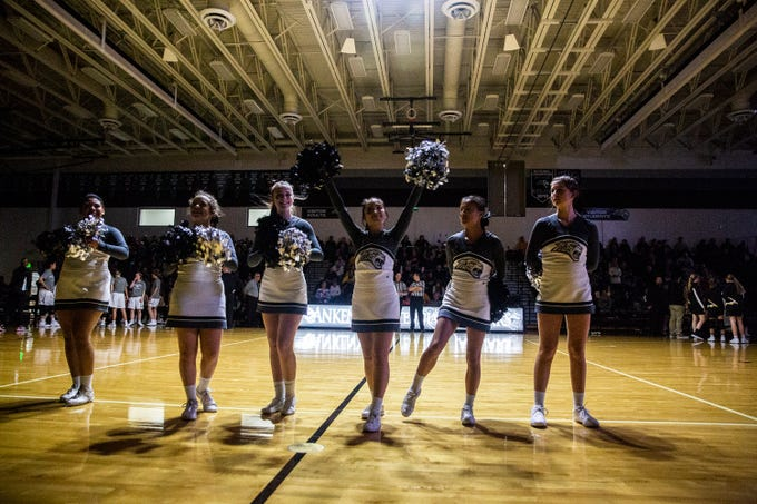 Centennial cheerleaders stand on the court before the start of the Southeast Polk vs. Ankeny Centennial girls' basketball game on Tuesday, Nov. 27, 2018, at Ankeny Centennial High School.