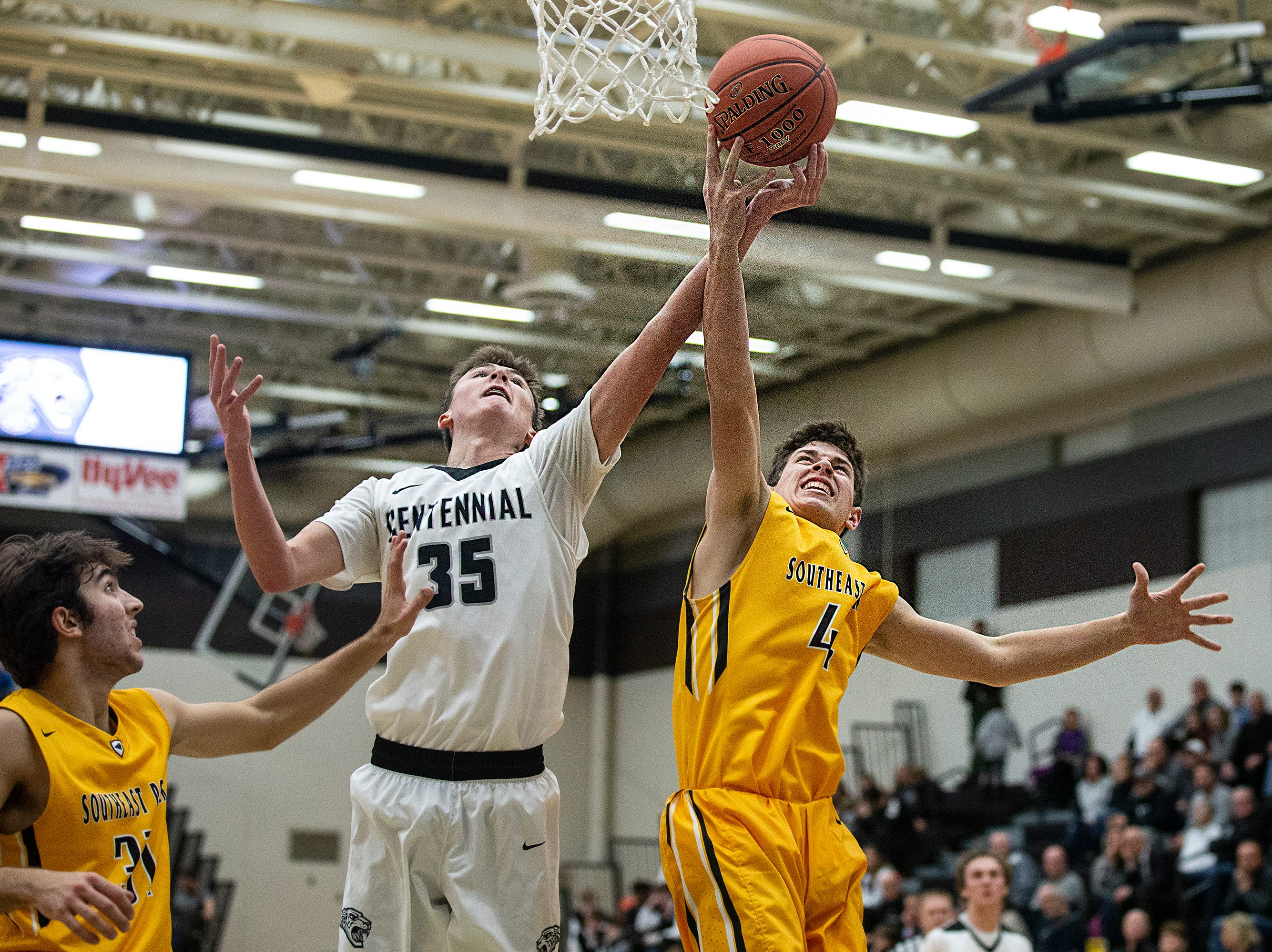 Centennial's Cody McCullough and SEP's Jaxon Dailey reach for a rebound during the Southeast Polk vs. Ankeny Centennial boy's basketball game on Tuesday, Nov. 27, 2018, at Ankeny Centennial High School.