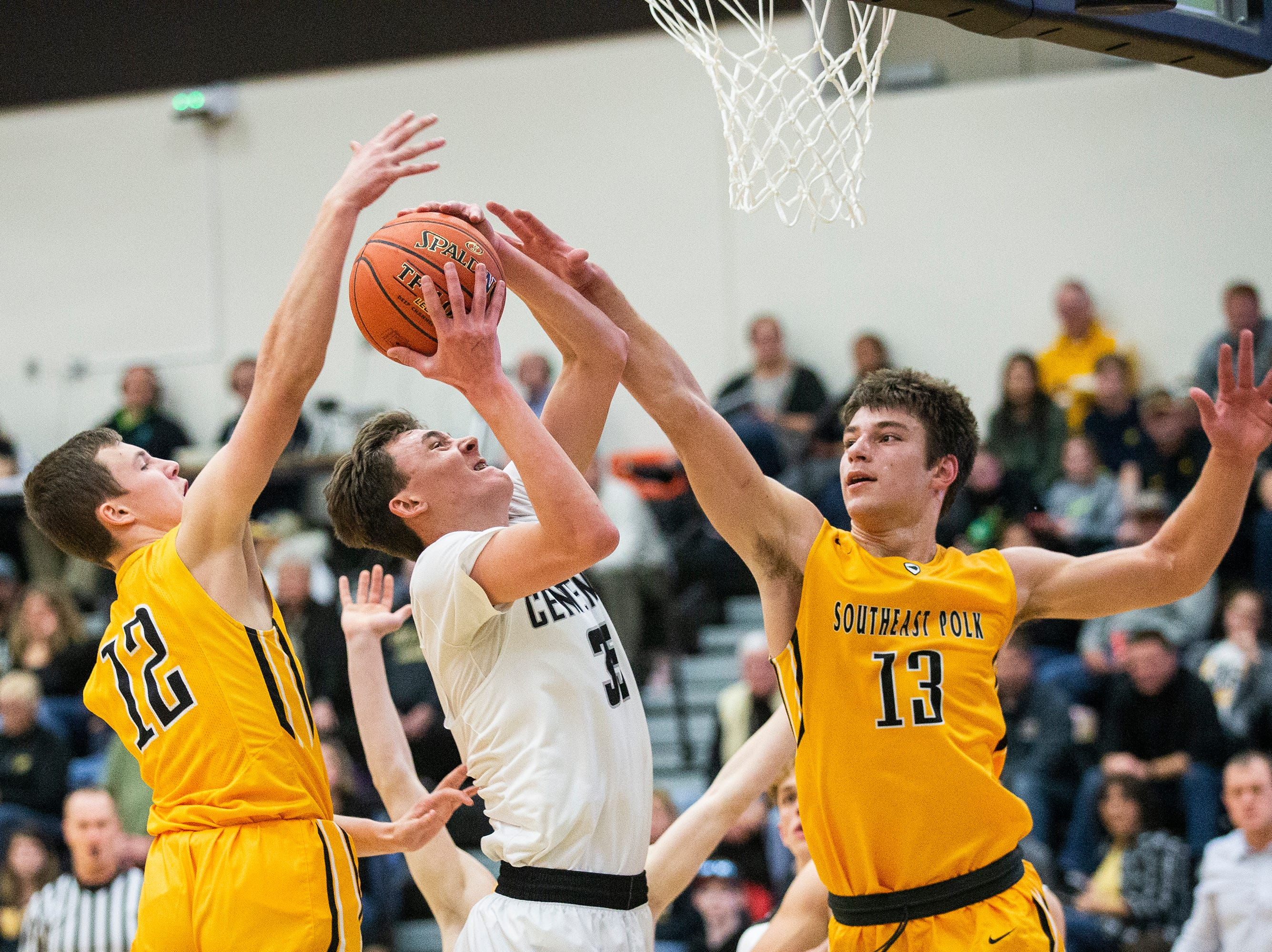 Centennial's Cody McCullough tries to shoot the ball against SEP defenders Fred Johnson and Dominic Caggiano during the Southeast Polk vs. Ankeny Centennial boy's basketball game on Tuesday, Nov. 27, 2018, at Ankeny Centennial High School.