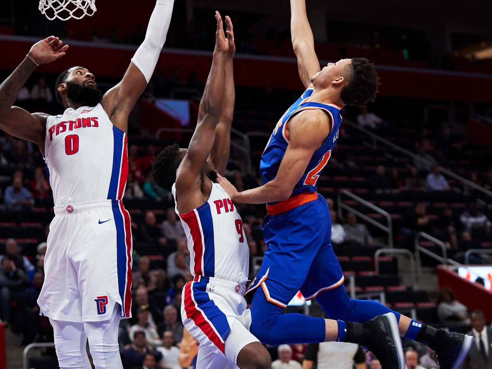 New York Knicks forward Kevin Knox (20) shoots on Detroit Pistons guard Langston Galloway (9) and center Andre Drummond (0) in the second half at Little Caesars Arena.