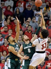 Louisville forward Jordan Nwora (33) shoots over the defense of Michigan State forward Kenny Goins (25) and forward Kyle Ahrens (0) during the first half of an NCAA college basketball game, in Louisville, Ky., Tuesday, Nov. 27, 2018.