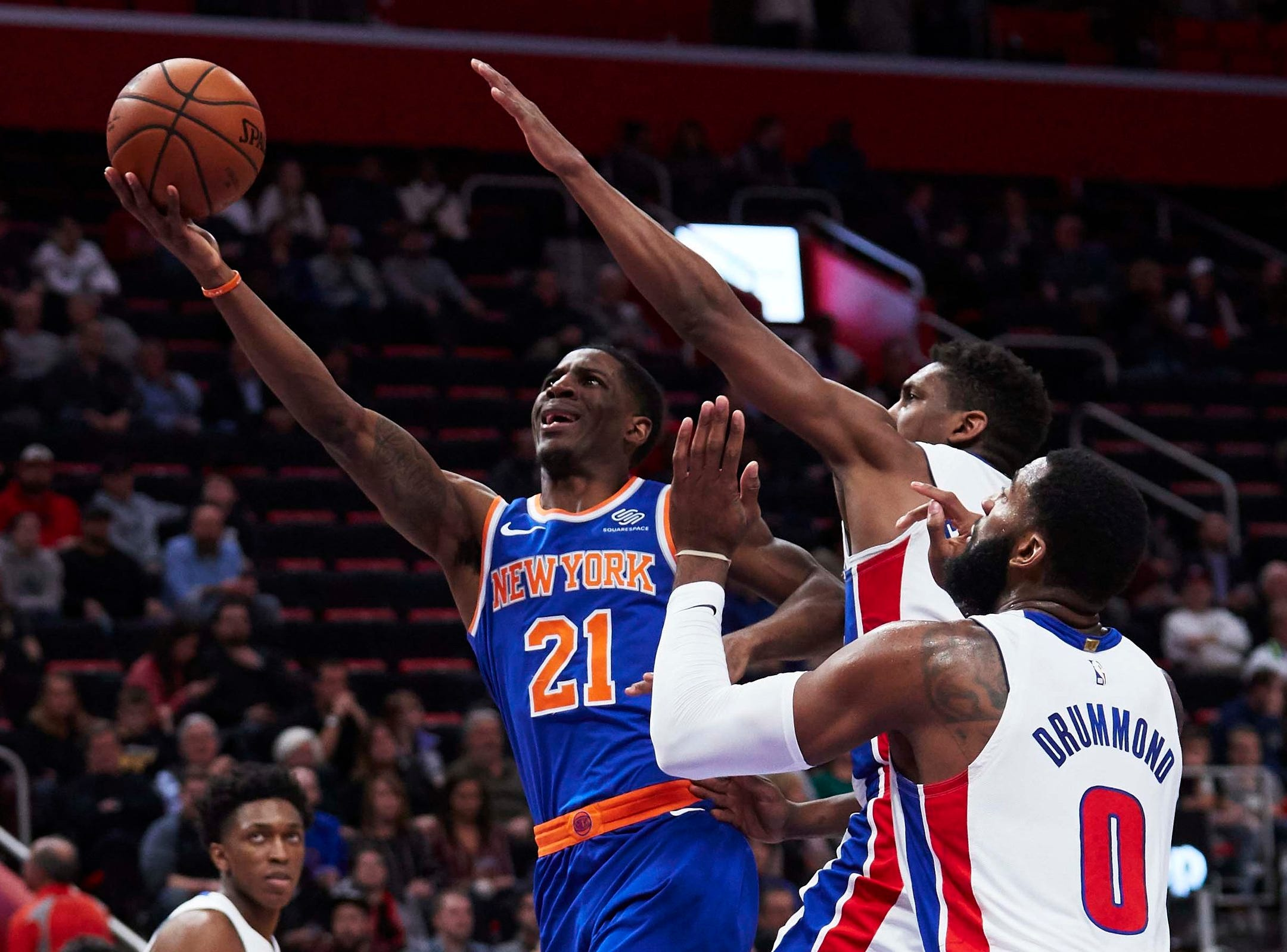 New York Knicks guard Damyean Dotson (21) goes to the basket on Detroit Pistons guard Langston Galloway (9) and center Andre Drummond (0) in the second half at Little Caesars Arena.