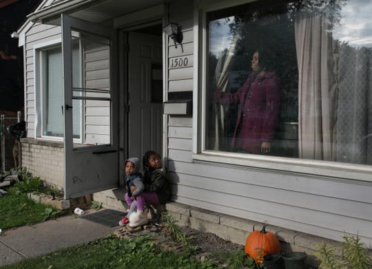Shalandra Jones- Scott looks out the window of her home while watching her grand children Samaar Jones, 1, from left and Sameer Jones, 6 in Detroit on Friday, October 19, 2018. Jones-Scott and her husband bought the home from a relative in 2015 but the relative had not paid the back taxes. The house was foreclosed and slated for auction this year but through a program started last year between the city of Detroit and the United Community Housing Coalition Scott-Jones will be able to get the deed of the home back for $1000.