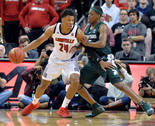 Louisville forward Dwayne Sutton (24) attempts to work his way around the defense of Michigan State guard Cassius Winston (5) during the first half of an NCAA college basketball game, in Louisville, Ky., Tuesday, Nov. 27, 2018.