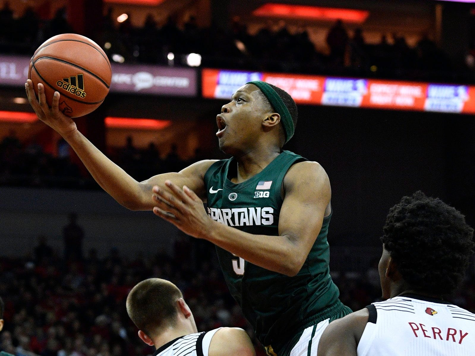 Michigan State Spartans guard Cassius Winston (5) shoots against Louisville Cardinals guard Ryan McMahon (30) during the first half at KFC Yum! Center.