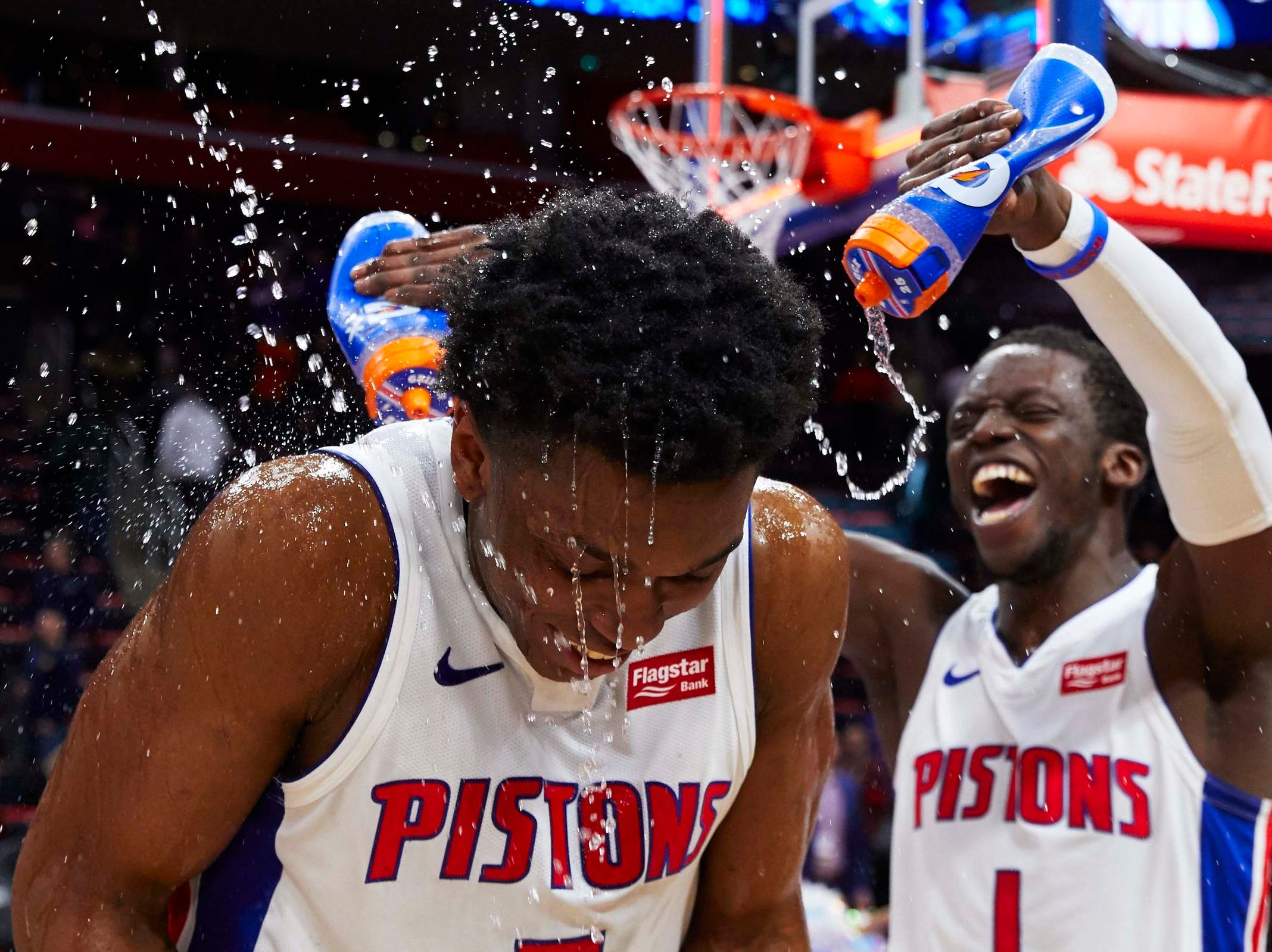 Detroit Pistons forward Stanley Johnson (7) is sprayed with water by guard Reggie Jackson (1) after the game against the New York Knicks at Little Caesars Arena.