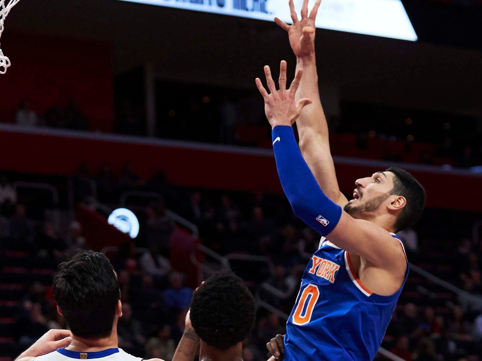 New York Knicks center Enes Kanter (00) shoots on Detroit Pistons center Zaza Pachulia (27) and guard Ish Smith (14) in the second half at Little Caesars Arena.