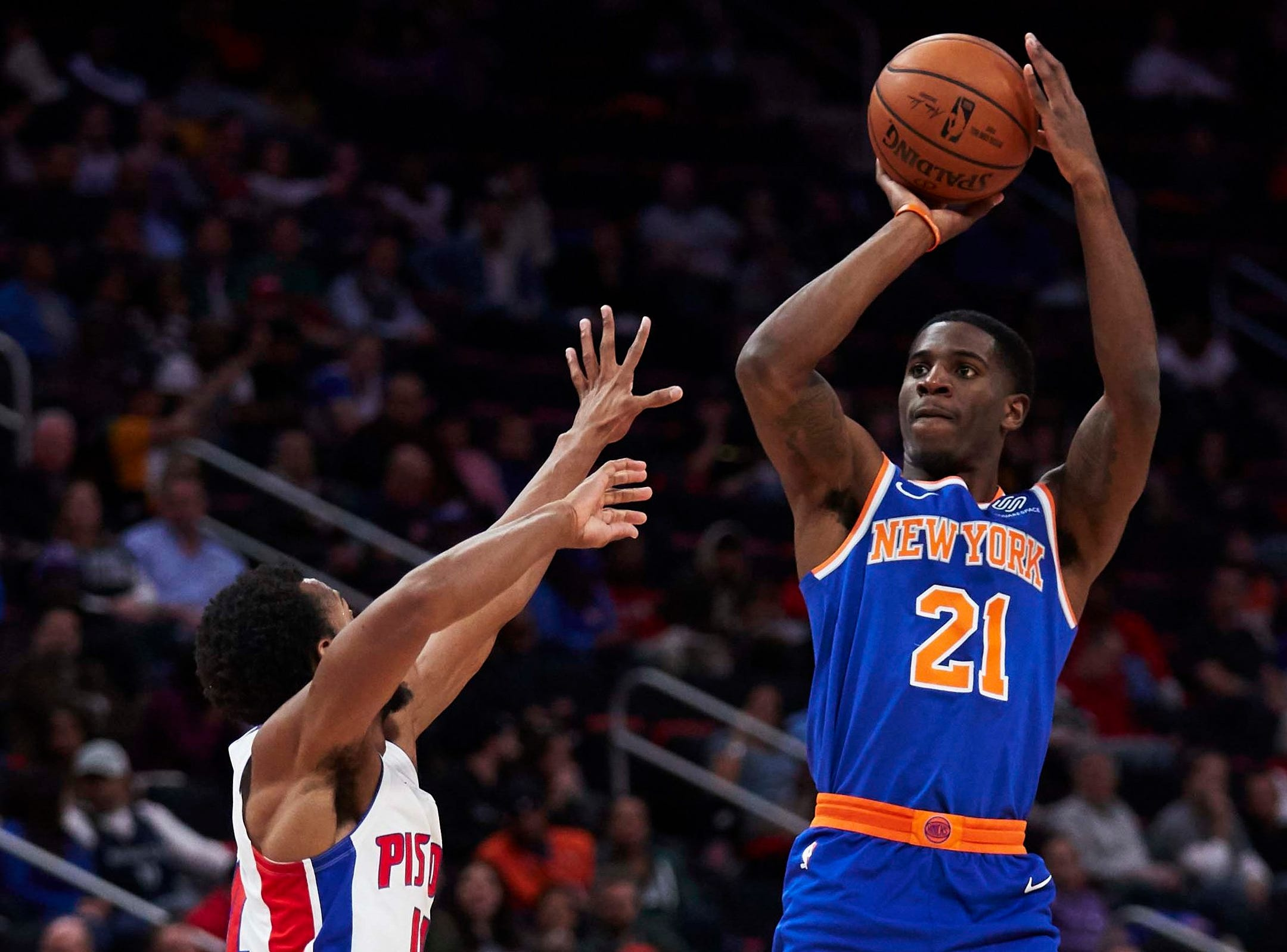 New York Knicks guard Damyean Dotson (21) shoots on Detroit Pistons guard Ish Smith (14) in the second half at Little Caesars Arena.