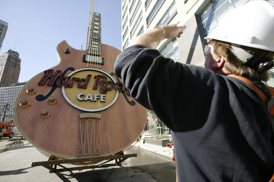Terry Davinney, a Metro Detroit Signs employee, monitors the lifting of a replica of famous Detroit rocker Ted Nugent's 35-foot Neon Gibson Byrdland Guitar at the Hard Rock Cafe in Detroit on Oct. 6, 2003.  (Photo by Regina H. Boone/Detroit Free Press)