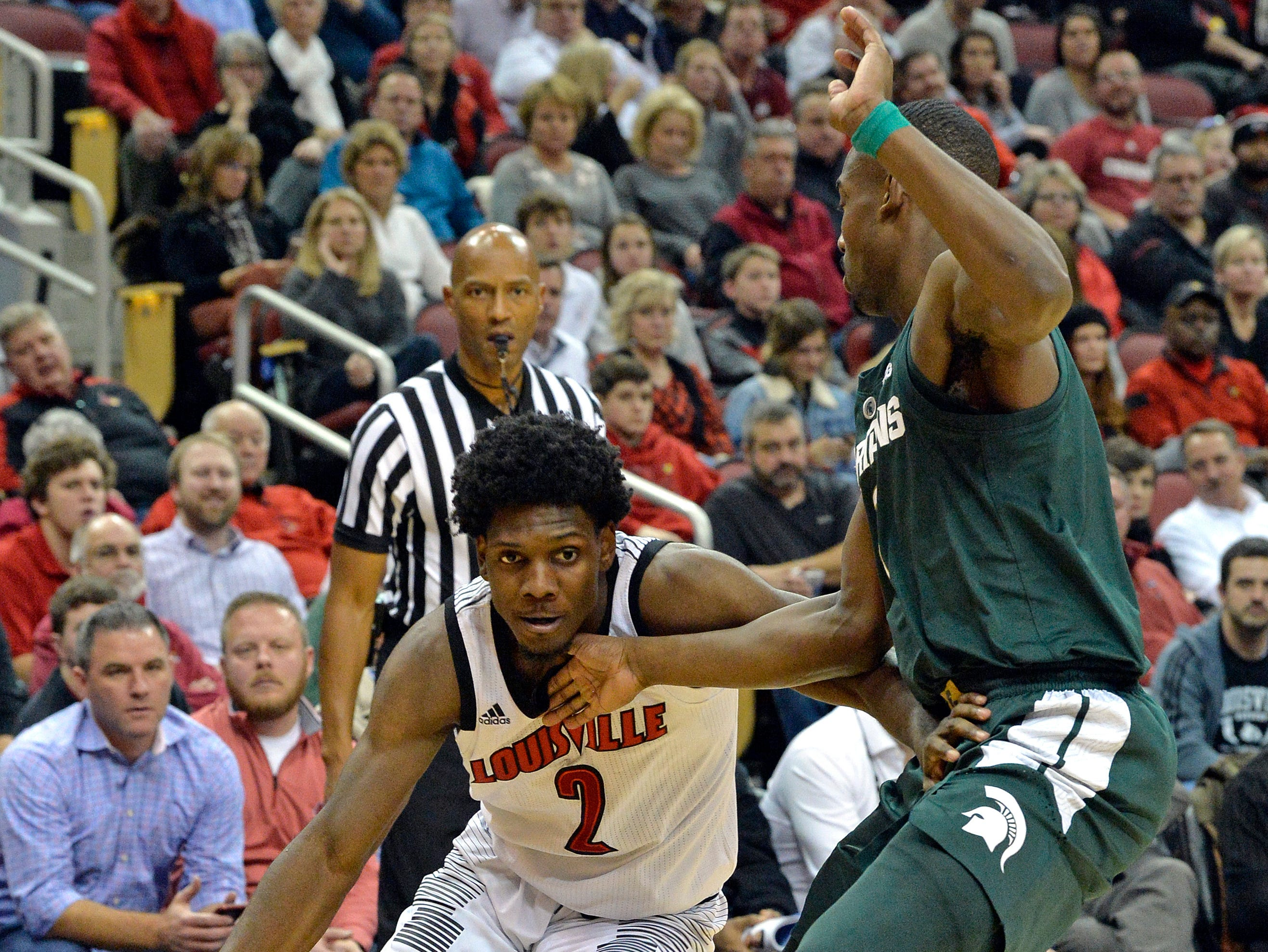 Louisville guard Darius Perry (2) attempts to drive past Michigan State guard Joshua Langford (1) during the overtime period.