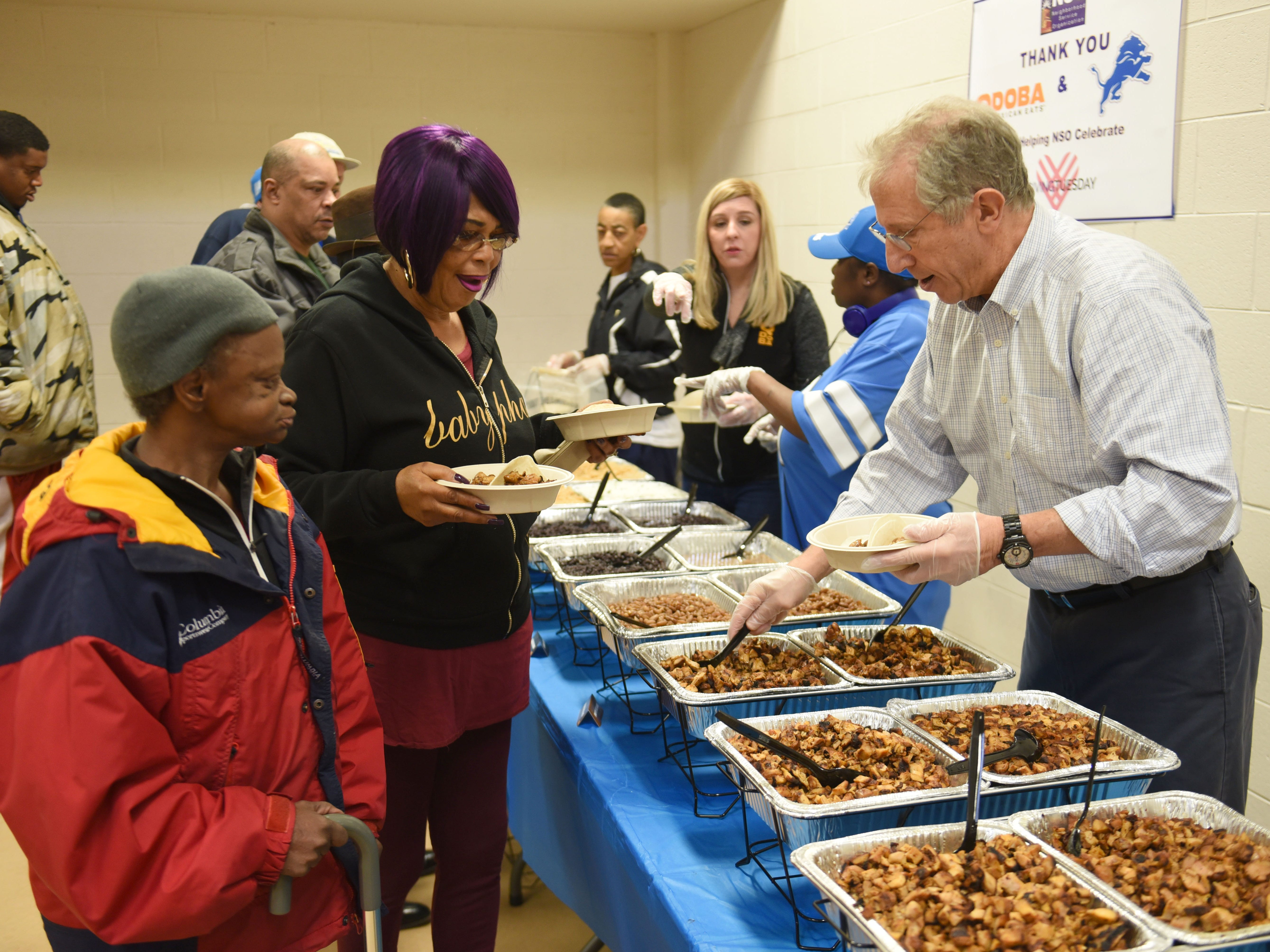 Dr. Richard Lichtenstein, right, chairman, Neighborhood Services Organization, serves clients a meal provided by Qdoba Mexican restaurant on Giving Tuesday.