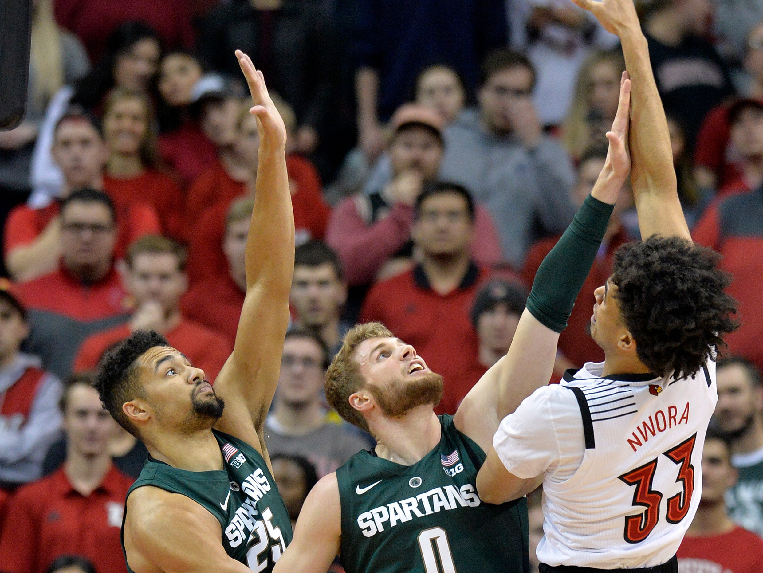 Louisville forward Jordan Nwora (33) shoots over the defense of Michigan State forward Kenny Goins (25) and forward Kyle Ahrens (0) during the first half.