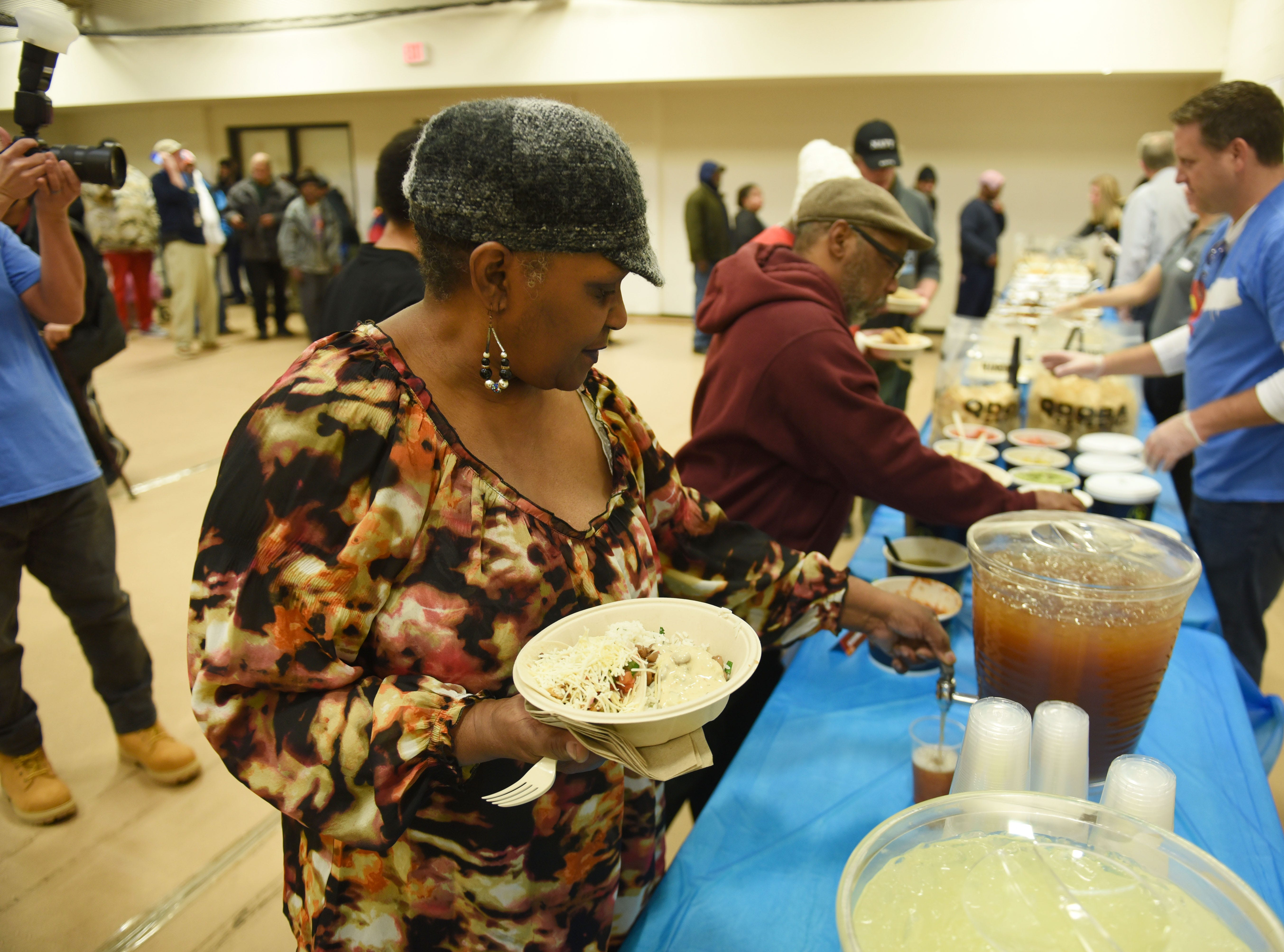 Betty Washington gets a beverage with her meal courtesy of Qdoba at Neighborhood Services Organization's offices in Detroit for Giving Tuesday on November 27, 2018.