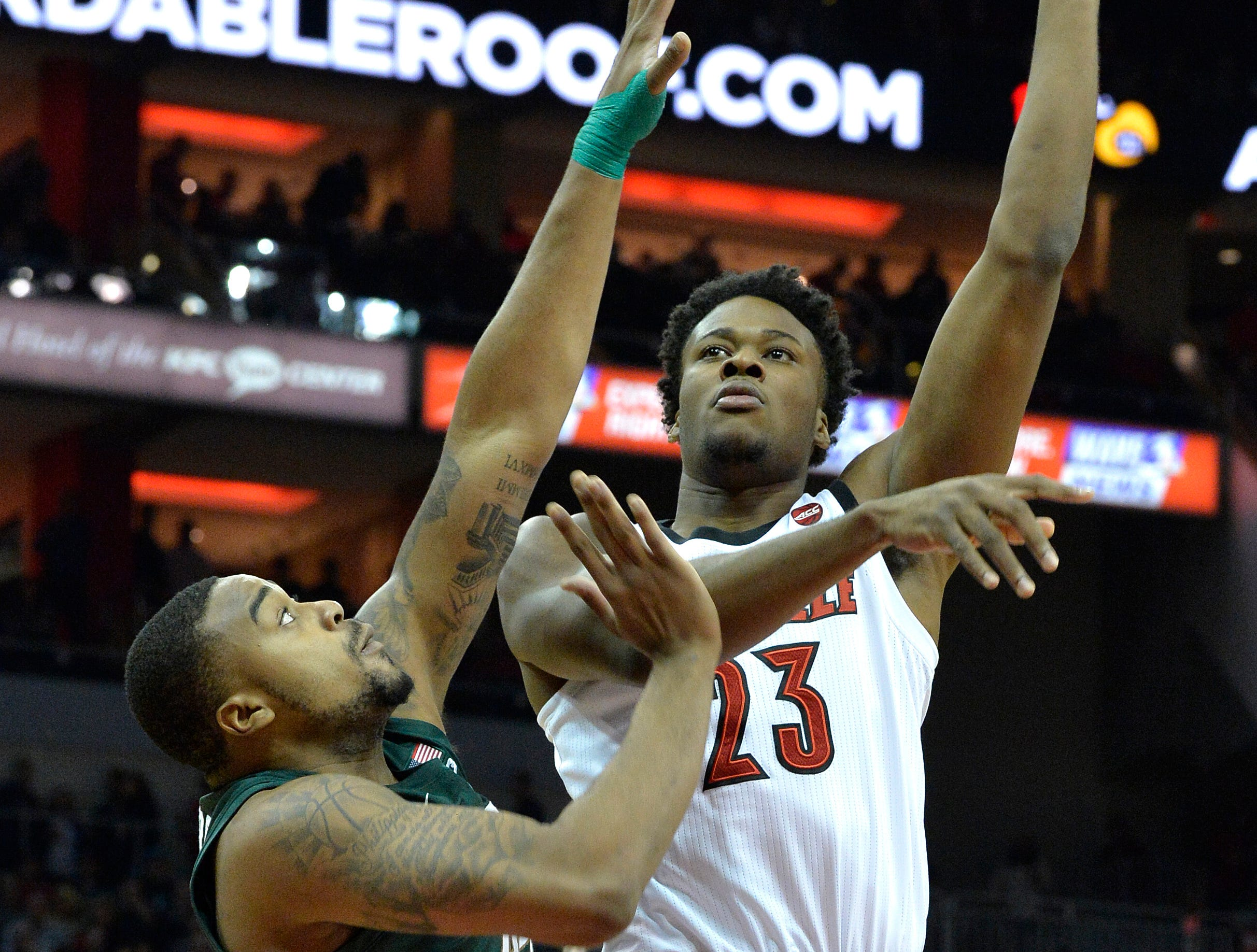 Louisville center Steven Enoch (23) shoots over the defense of Michigan State forward Nick Ward (44) during overtime.