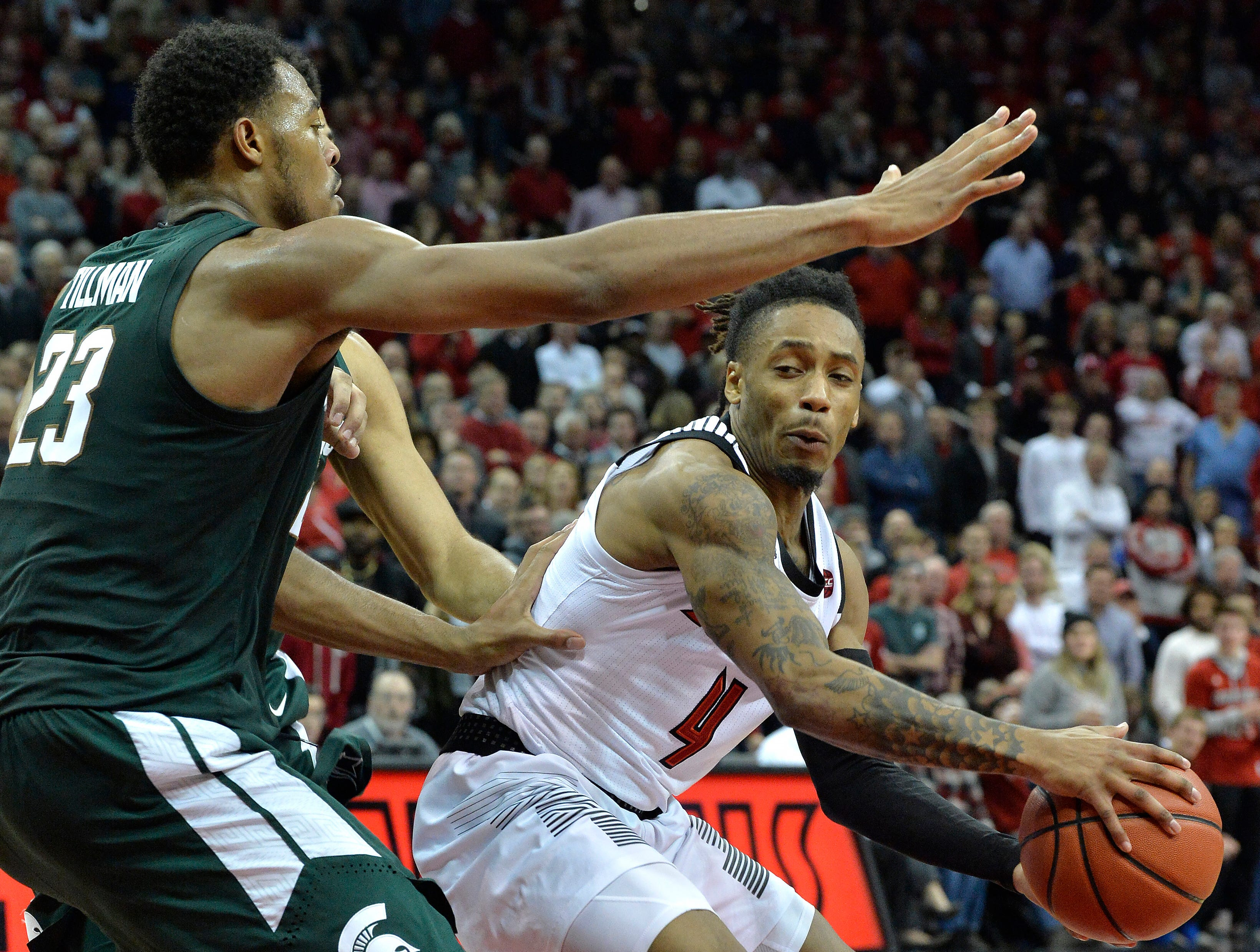 Louisville guard Khwan Fore (4) attempts to keep the ball away from the defense of Michigan State forward Xavier Tillman (23) during the second half.