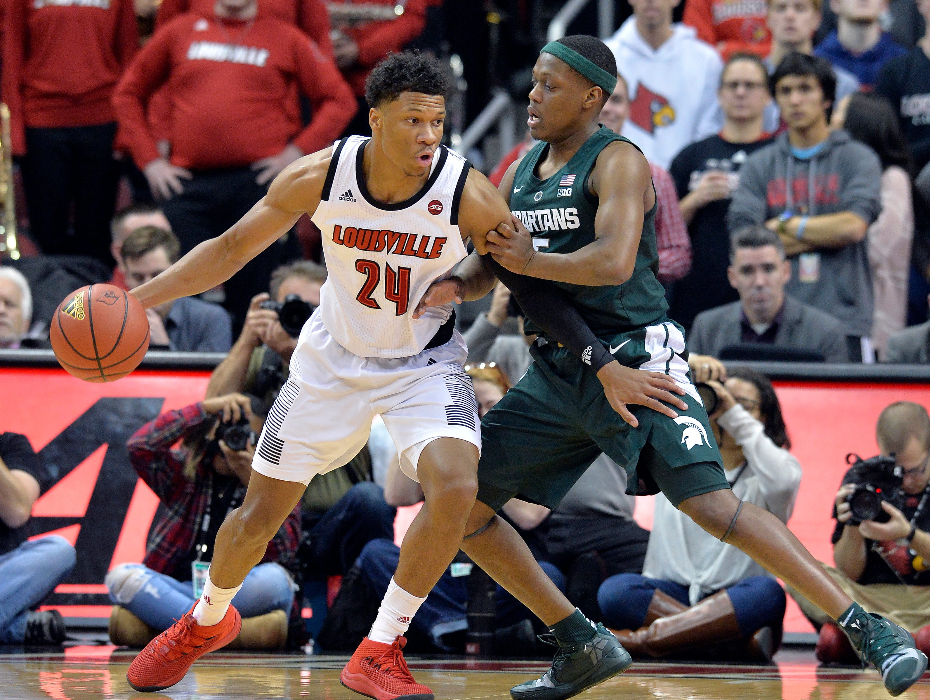 Louisville forward Dwayne Sutton (24) attempts to work his way around the defense of Michigan State guard Cassius Winston (5) during the first half.