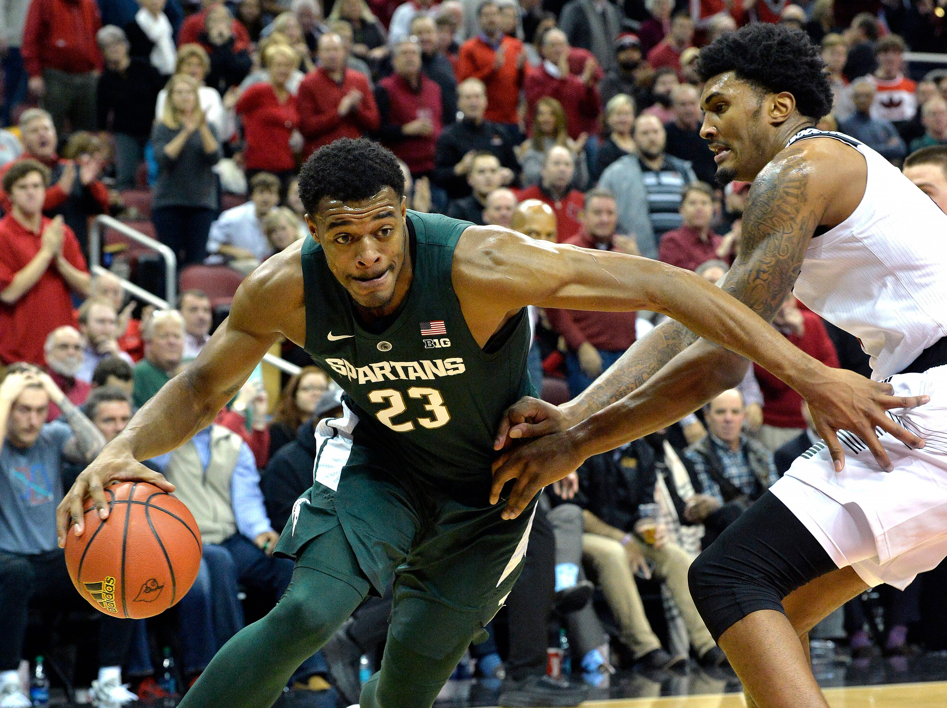 Michigan State forward Xavier Tillman (23) attempts to drive past the defense of Louisville center Malik Williams (5) during the first half.
