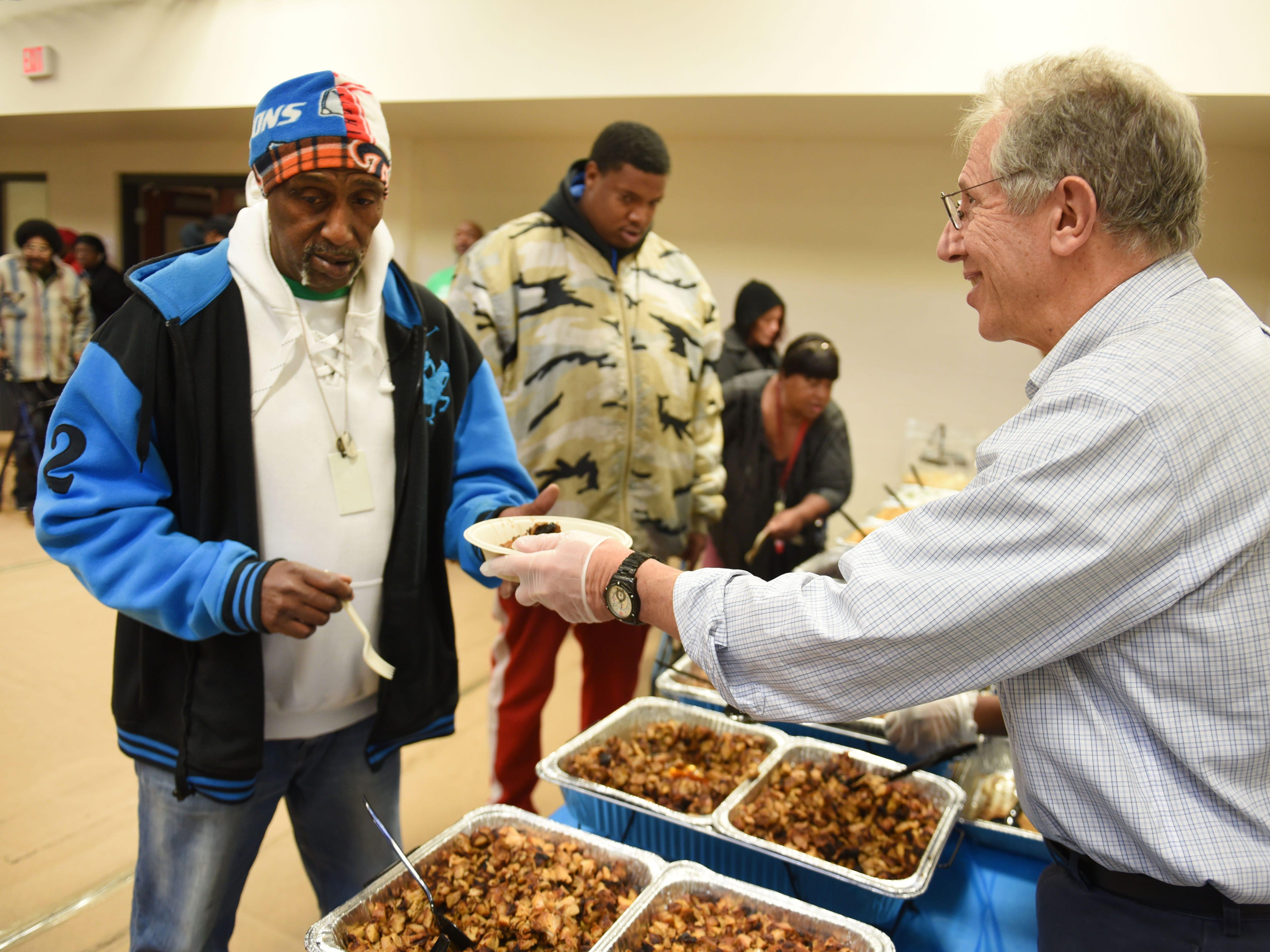 Dr. Richard Lichtenstein, chairman, Neighborhood Services Organization, serves client Clifford Lamar.