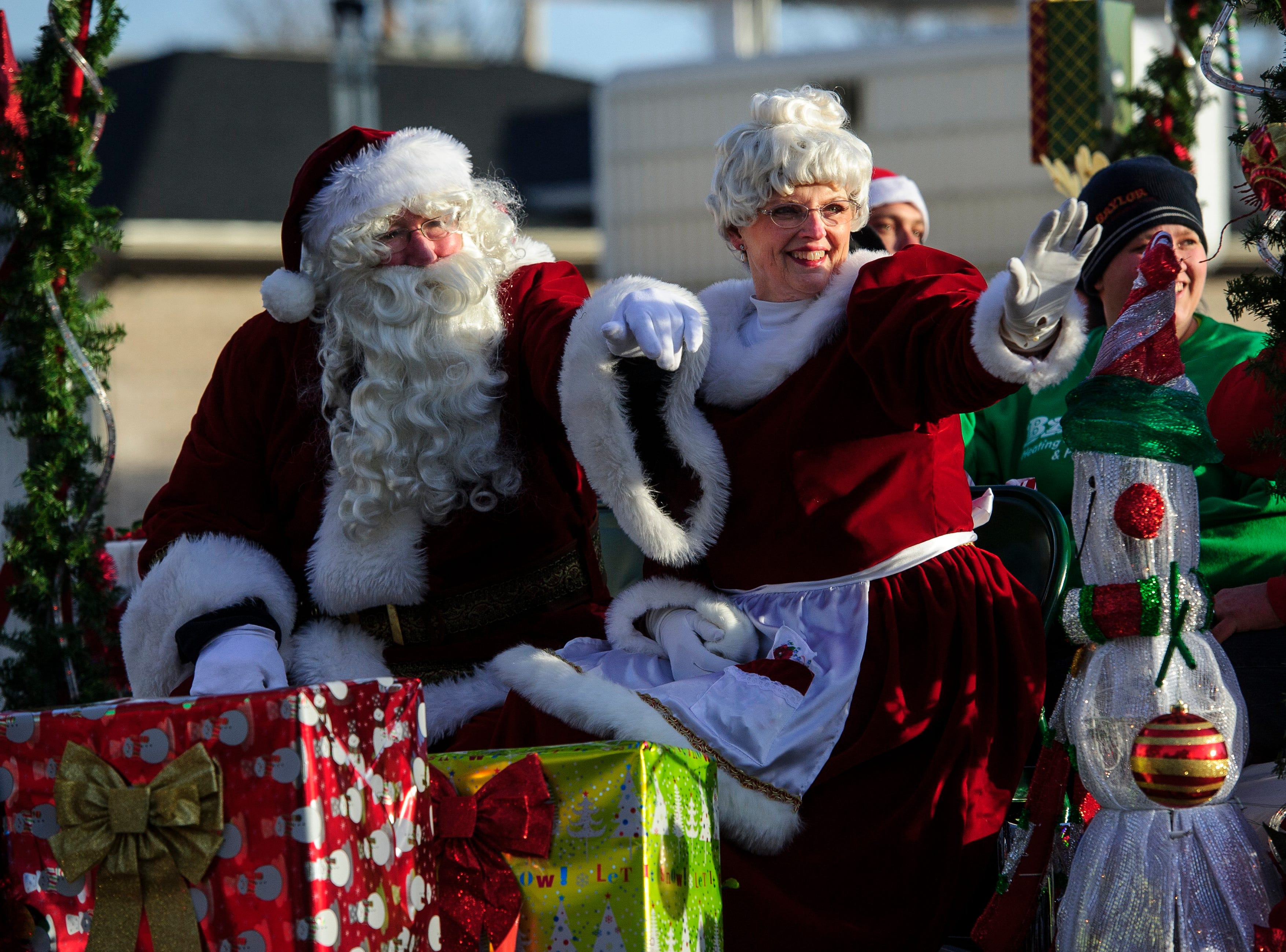 Santa and Mrs. Claus wave to bystanders from a float in the Christmas Parade at North Main Street in Evansville, Ind., on Sunday, November 24, 2013.