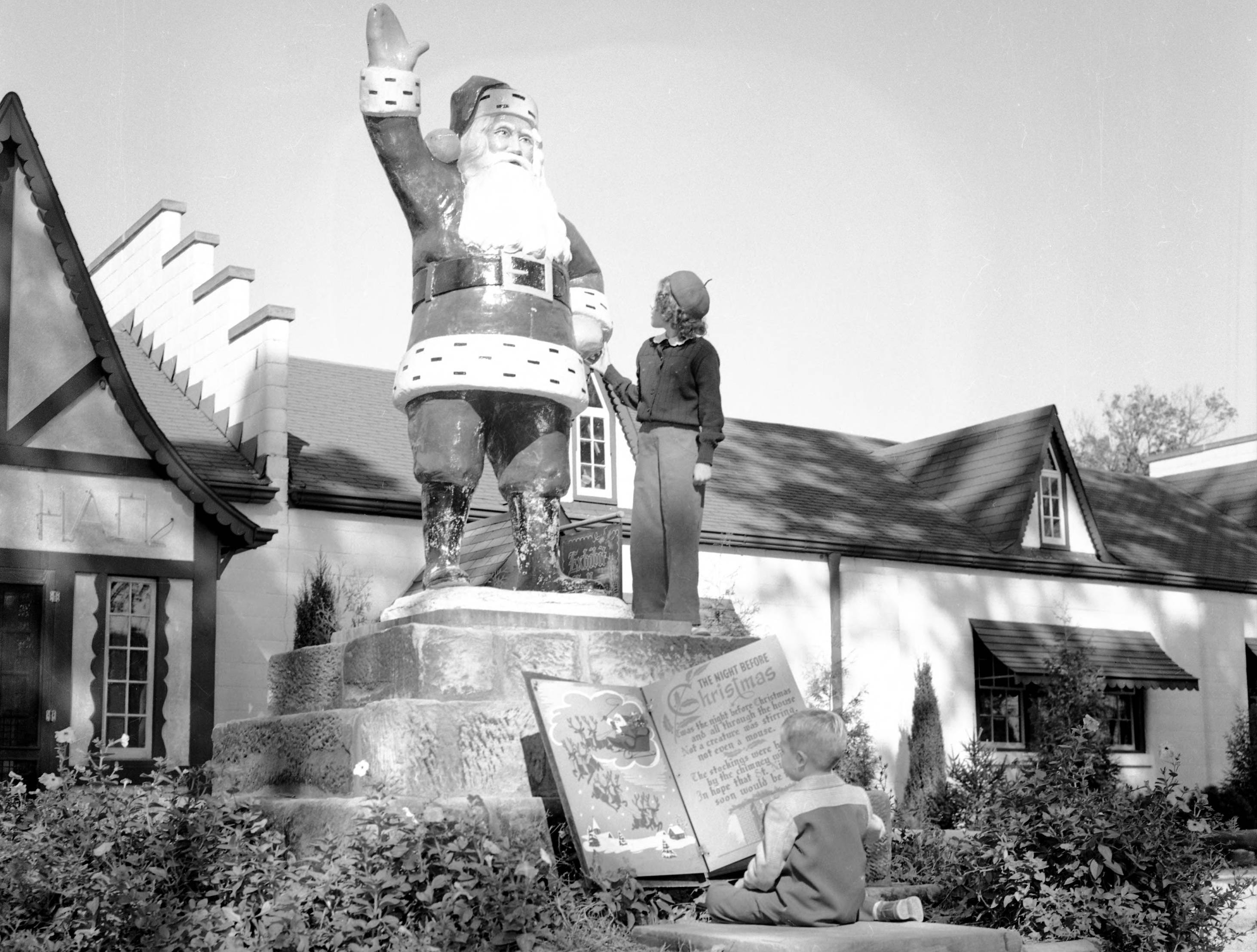Statue of a waving Santa Claus, with a young girl touching his hand.  In front is a extra large copy of Clement Clarke Moore's  A Visit from St. Nicholas, also known as The Night Before Christmas, with a young boy sitting in front of it, reading.  The Exhibit Hall portion of the village is behind the statue in 1949. Taken at Santa Claus Land, now known as Holiday World & Splashin' Safari.