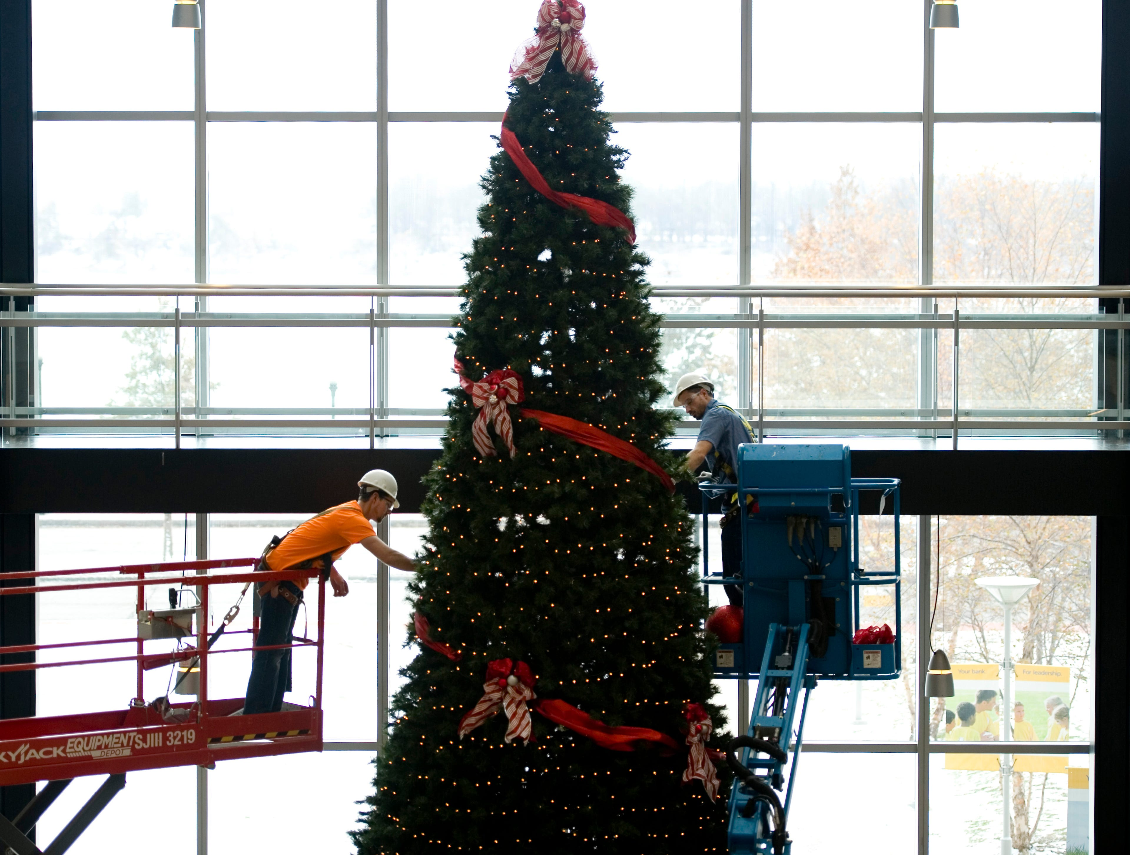 Industrial Contractors employees Brian Wagner (left) and Frank Martin decorate the Hospice Reflection Tree using bucket lifts in the lobby of Old National Bank Monday afternoon. The 37-foot-tall tree is used by the Deaconess Foundation to raise money for funding hospice bereavement programs, hospice services and equipment.