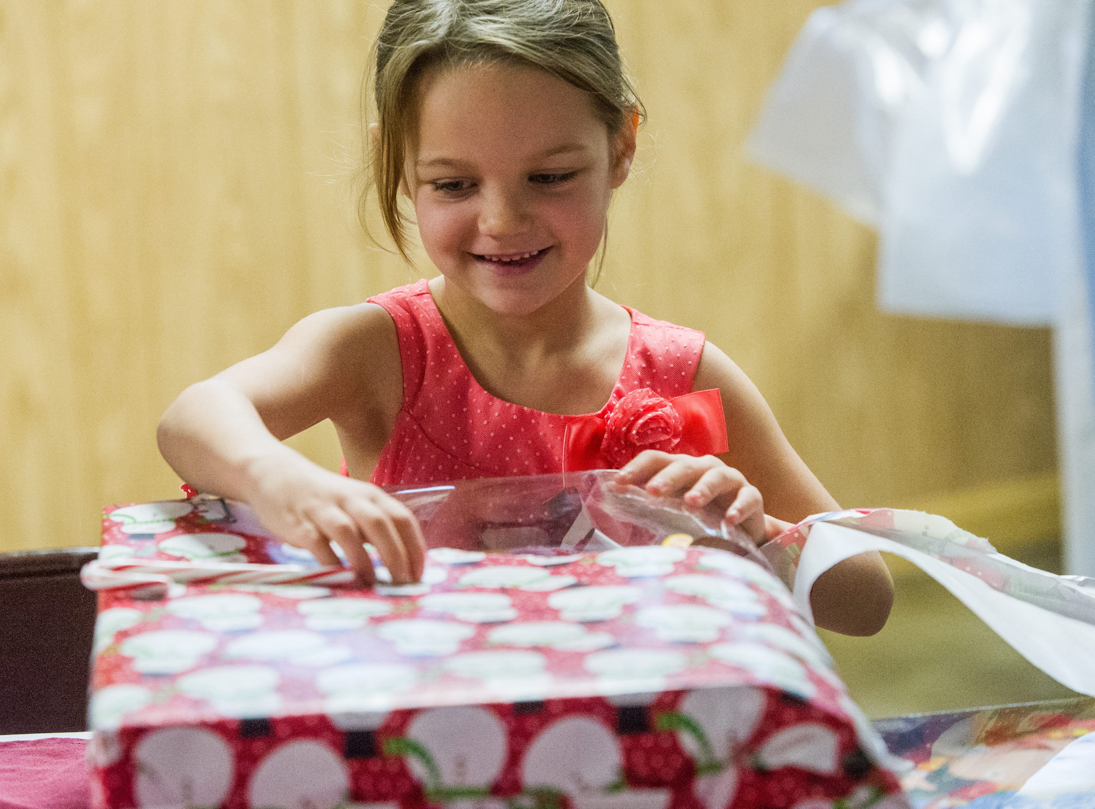 Five year-old Anna Newbold is all smiles as she unwraps one of her gifts from Santa at the annual Kids Christmas Party at the FOP Lodge in Evansville, Ind. Saturday, Dec. 12, 2015.