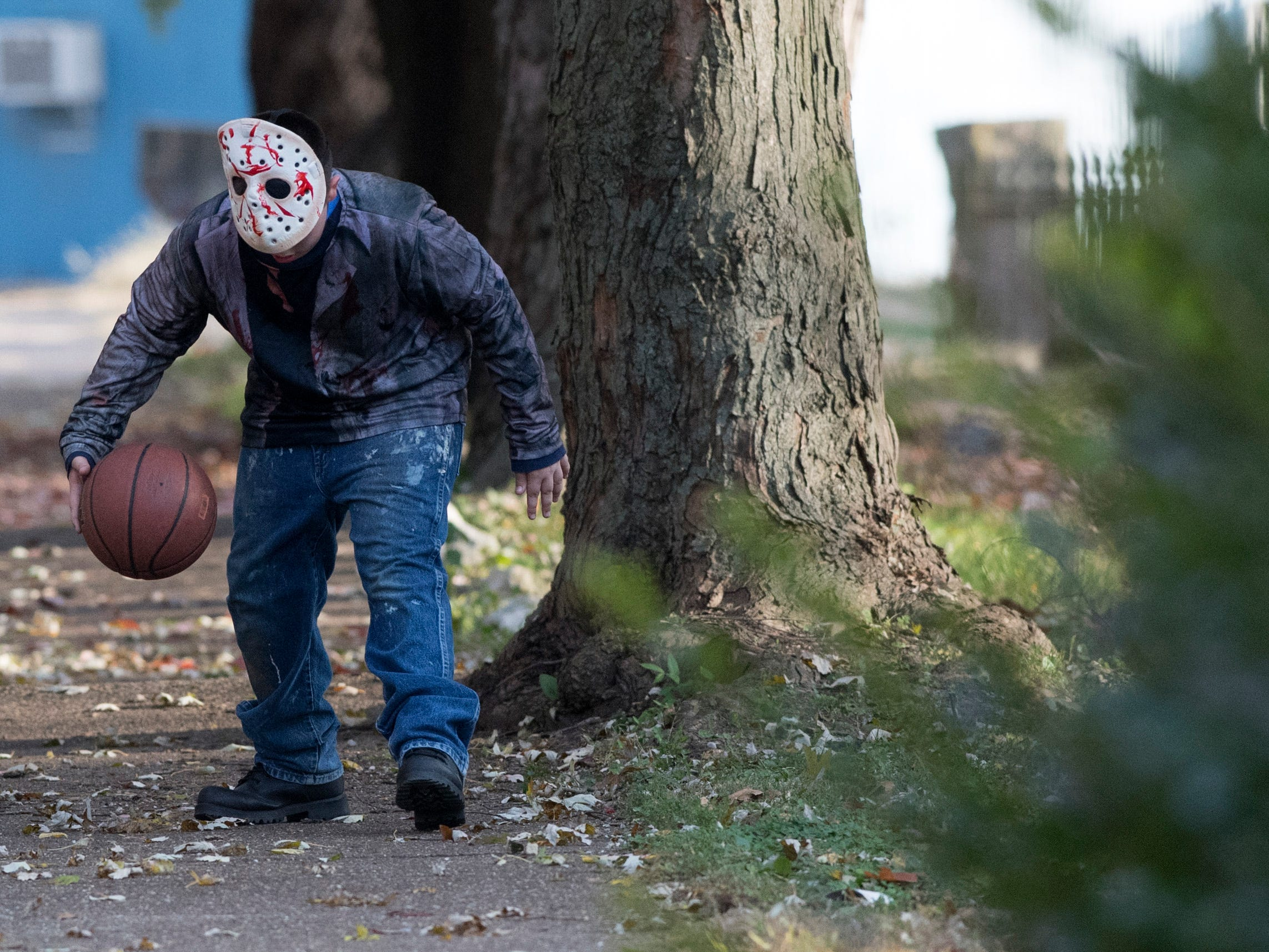 Micheal Blais dressed as Jason Voorhees dribbles a basketball before heading out to trick-or-treat, Tuesday, Oct. 30, 2018.