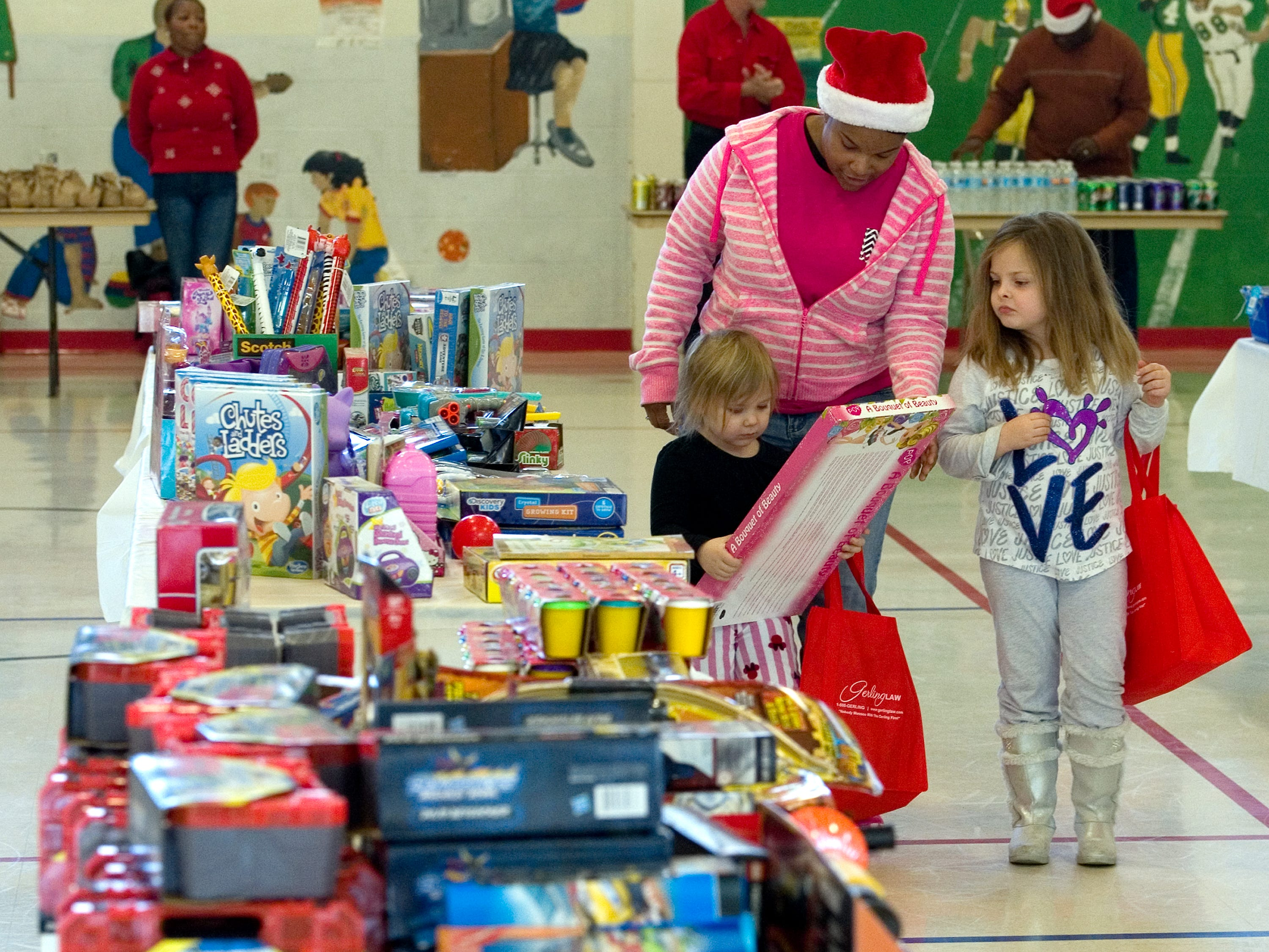 "Miley Wire, 7, (right) looks at the toy picked out by Cordillia Belwood, 3, (left) as they walk around the toys with volunteer Jamicka Holland during the 15th Annual ""Christmas in the Hood""  at the CK Newsome Center in Evansville, Ind. on Saturday morning, Dec. 19, 2015. This is Holland's second year as a volunteer for the event. Along with a visit with Santa the children were allowed to pick out a toy and were given fruit, cookies and other treats. The event is sponsored by the Coalition of Inner-city Neighborhoods (C.O.I.N.). Children also had a chance to win one of five boys' bikes and five girls' along with some tricycles that were to be given away at the end of the event."