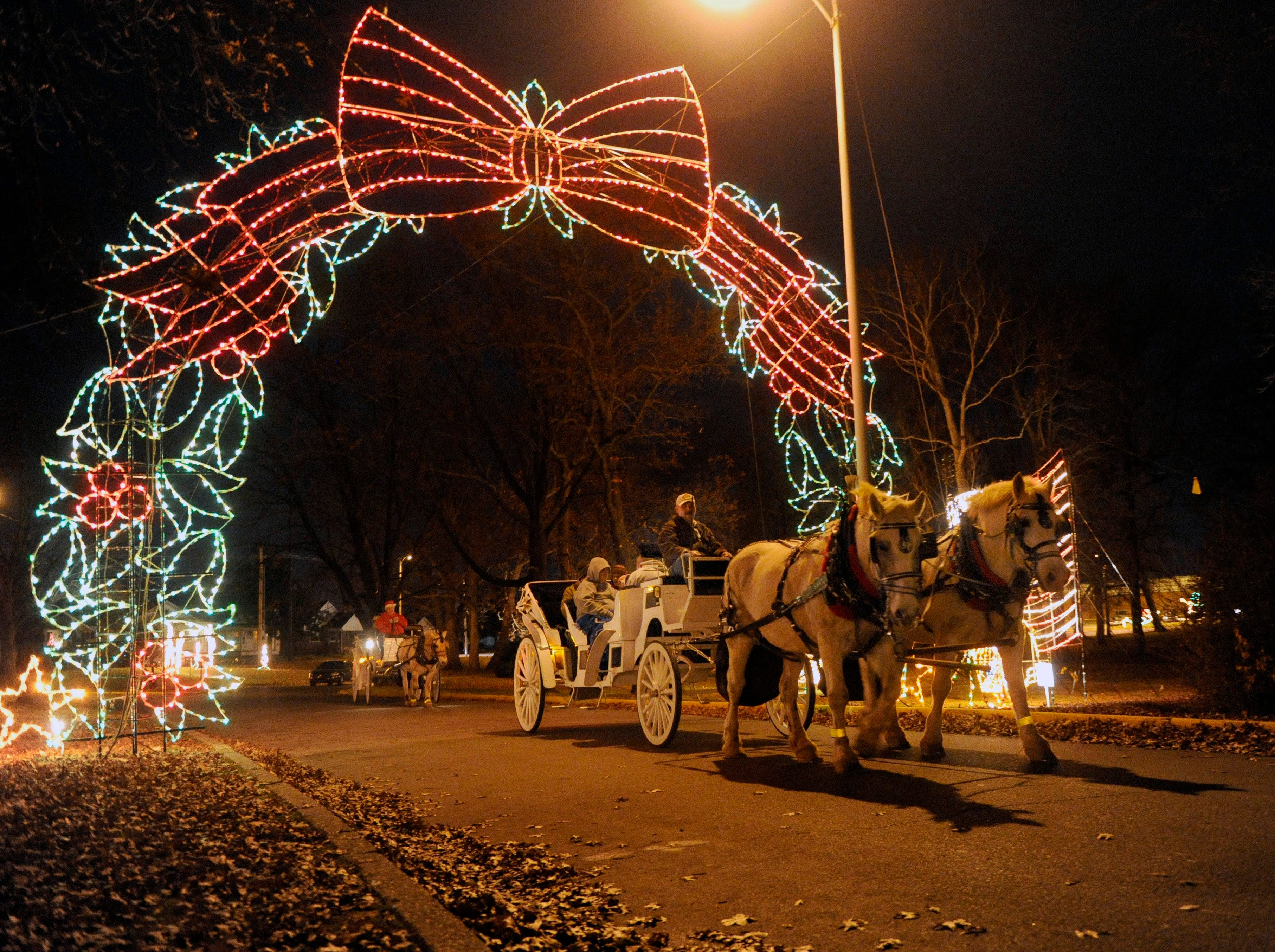 Families take a ride in a horse drawn carriage as they view the Fantasy of Lights show at Garvin Park in Evansville, Thursday evening, November 22, 2012. Carriage rides are available for $30, including a wheelchair accessible carriage if needed.